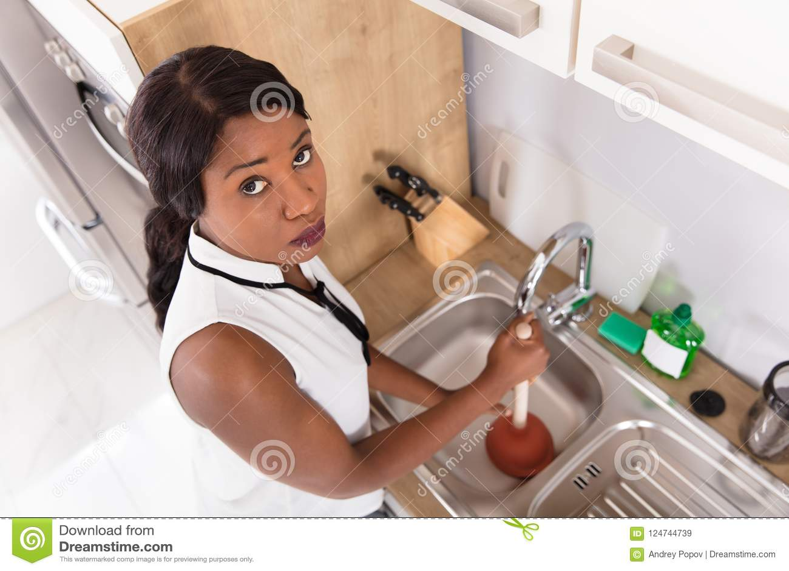 Donna infelice che utilizza tuffatore nel lavandino ostruito