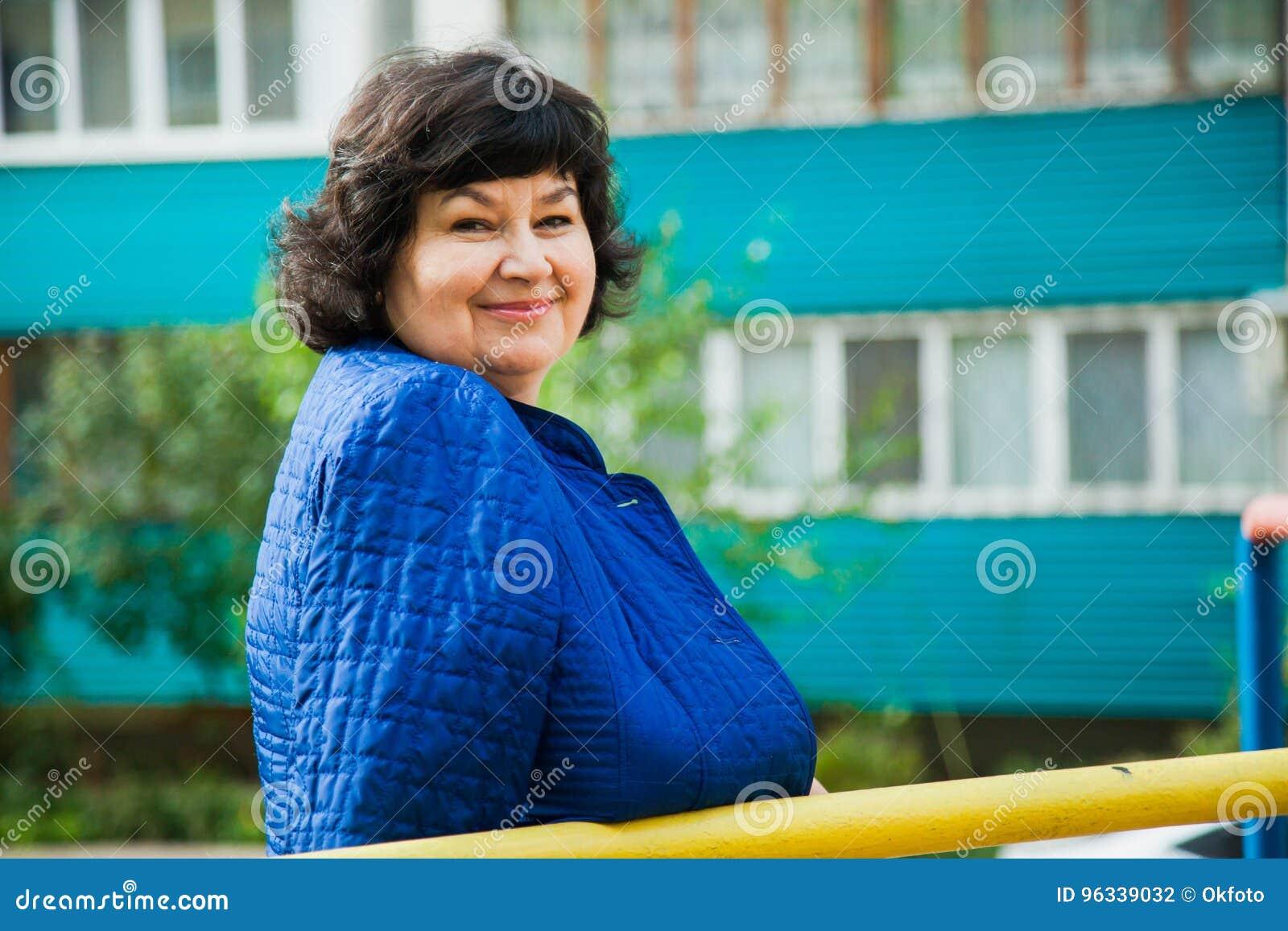 Donna invecchiata mezzo fra le costruzioni di appartamento della città