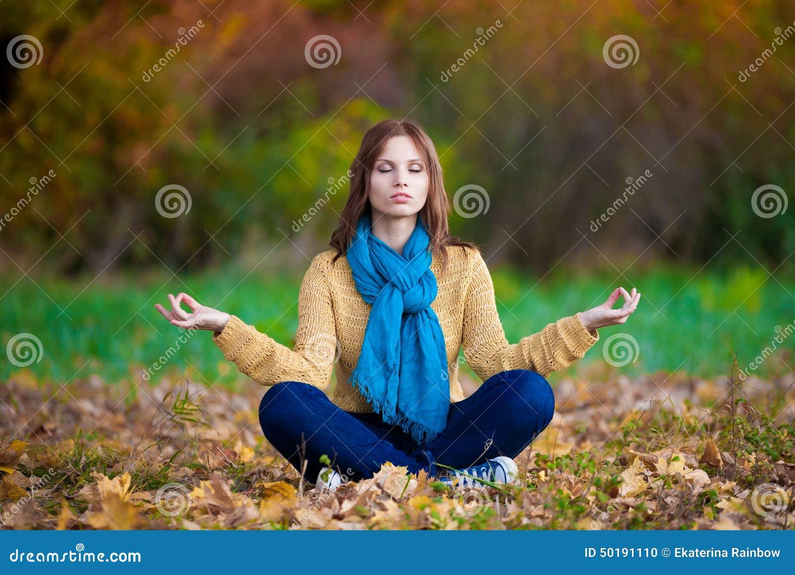 Donna in maglione, in blue jeans e nella meditazione beige della sciarpa