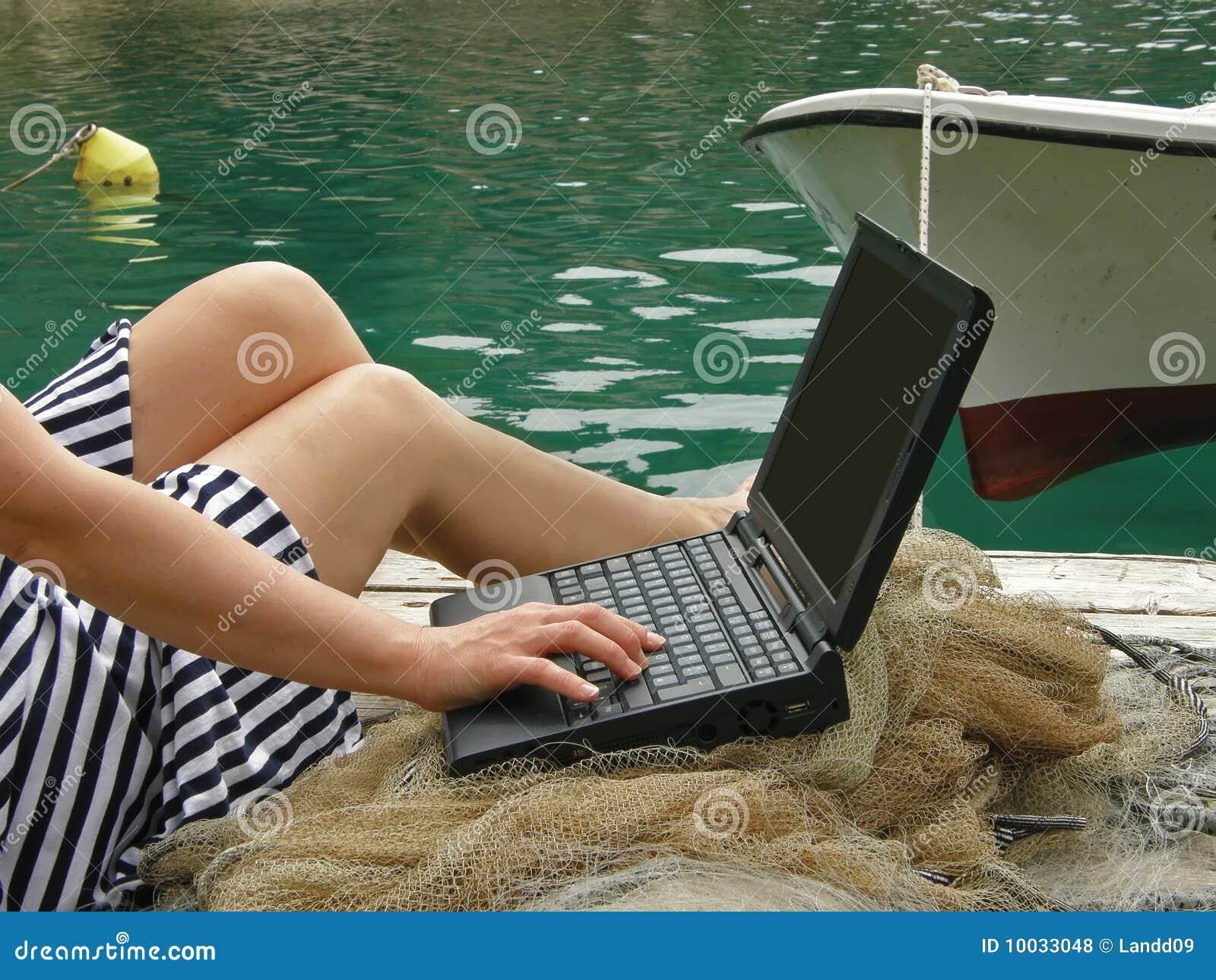Donna, marinaio, lavoro del falò sul computer portatile