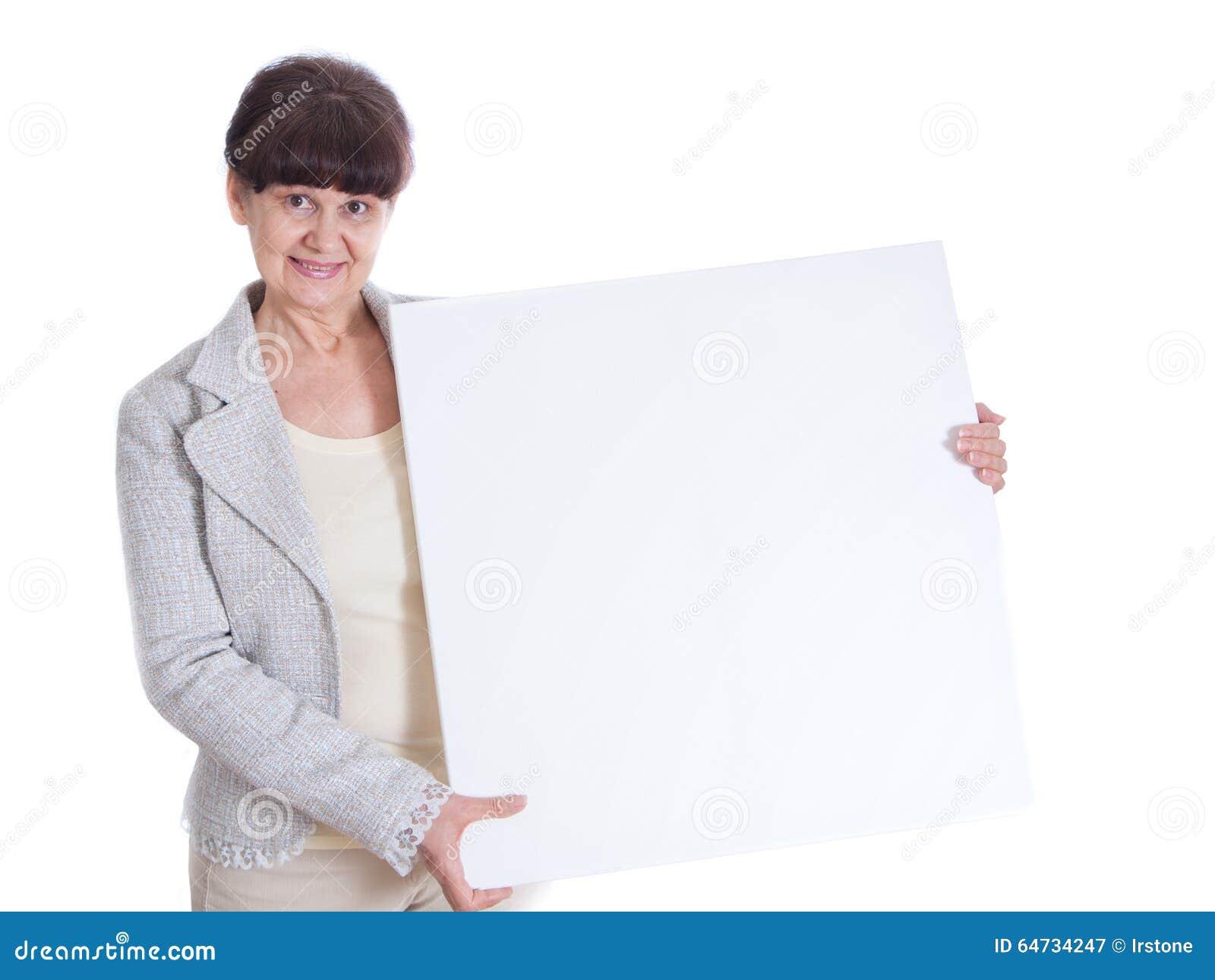 Donna matura che si appoggia insegna bianca Ritratto contro di fondo bianco