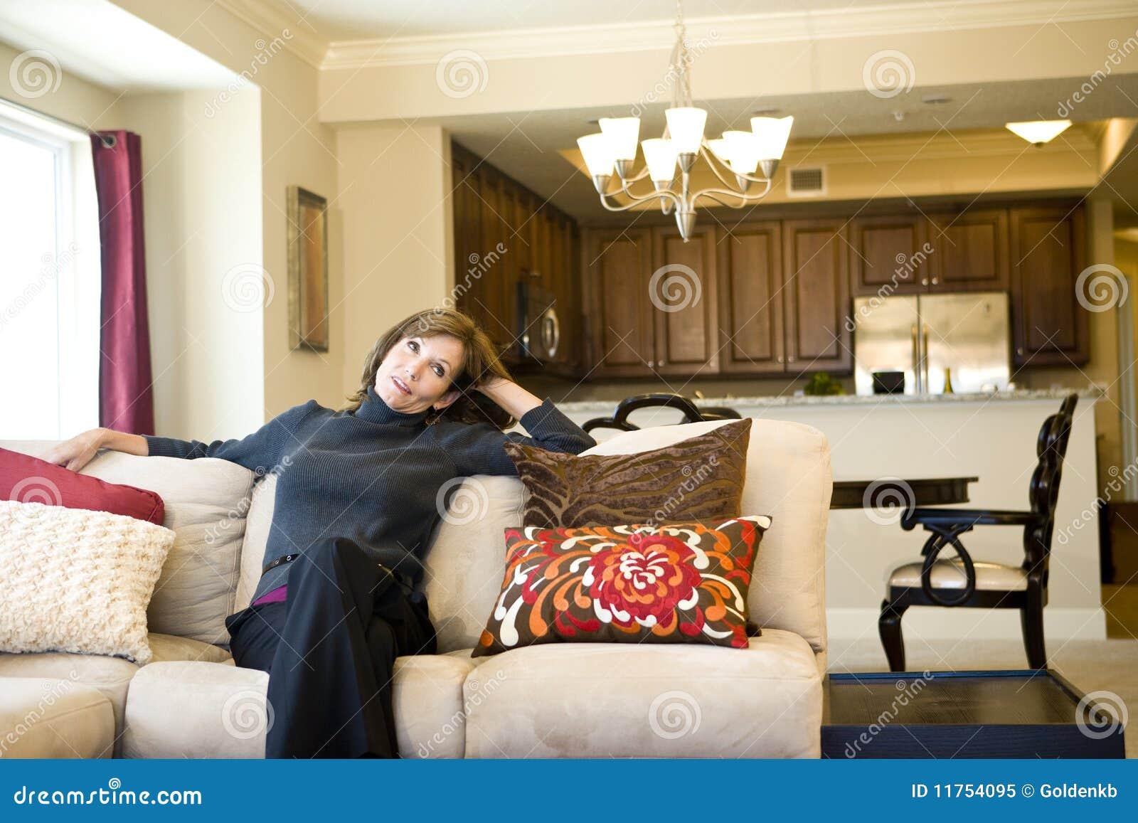 Donna matura che si distende sul sofà del salone