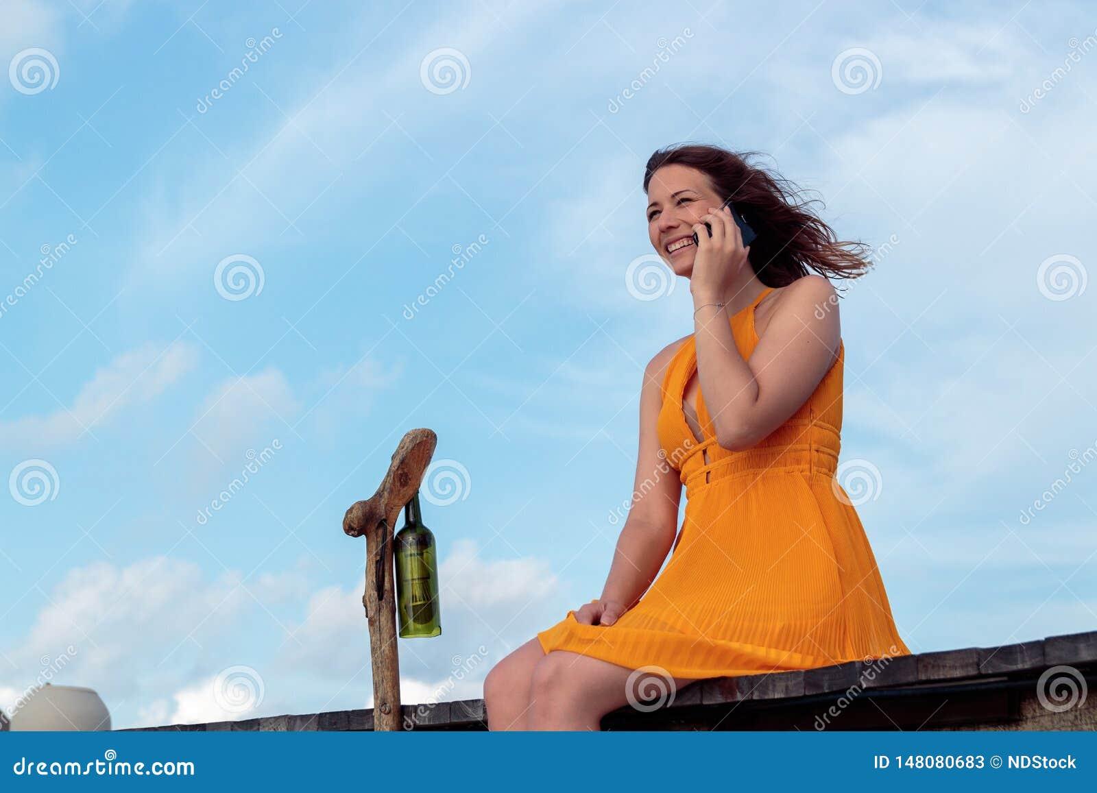 Donna messa su un pilastro in una posizione tropicale facendo uso del suoi smartphone e sorridere Cielo con le nuvole come fondo