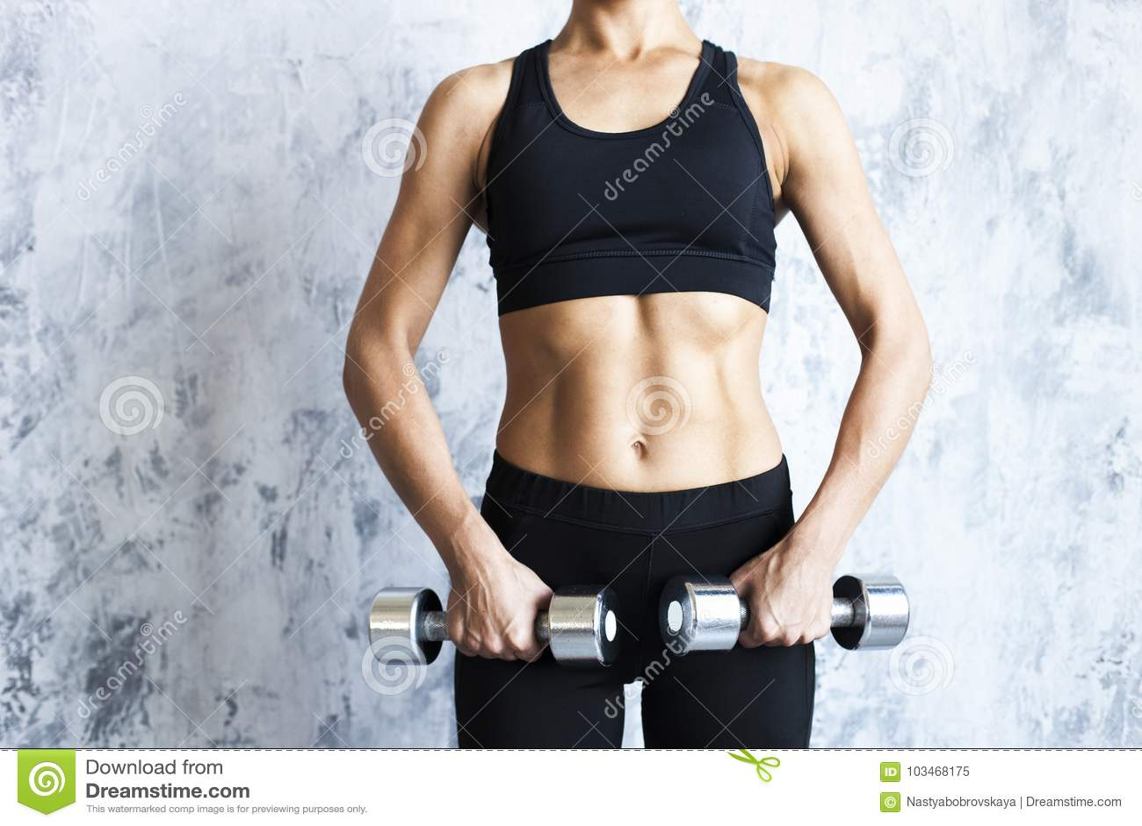 Donna muscolare con i bilancieri sulla parete strutturata