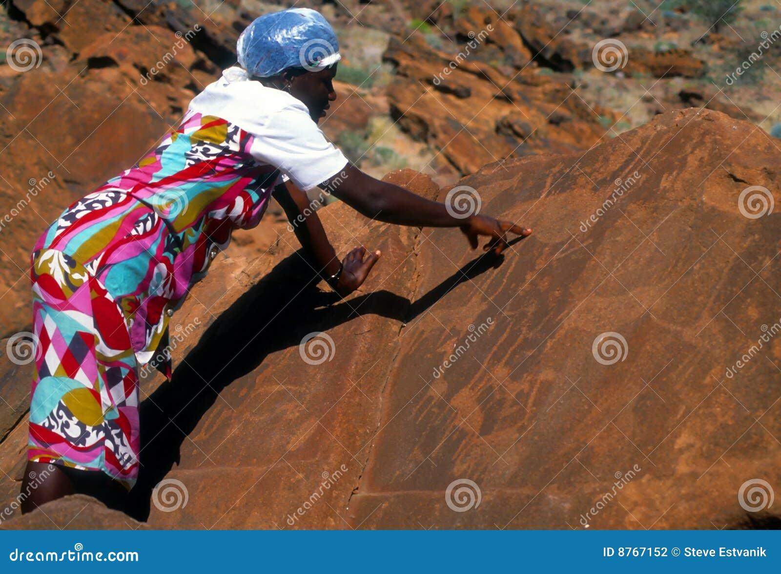 Donna namibiana che mostra le sculture preistoriche