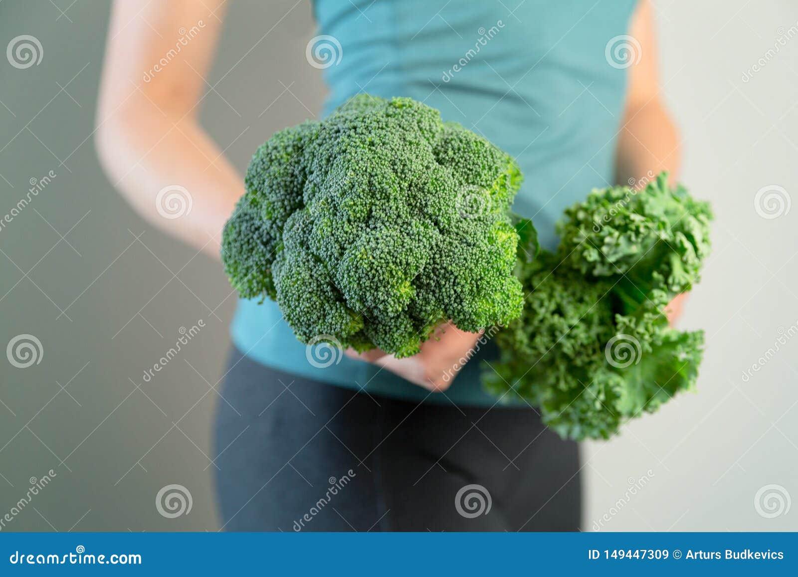 Donna nell usura di sport che tiene i broccoli e cavolo Stile di vita sano, donna che mangia alimento sano, stante a dieta