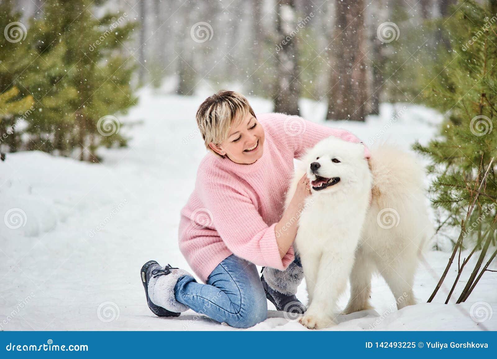 Donna nella foresta di inverno che cammina con un cane La neve sta cadendo