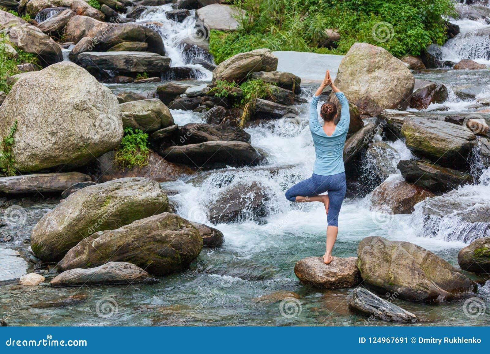 Donna nella posa dell albero di Vrikshasana di asana di yoga alla cascata all aperto