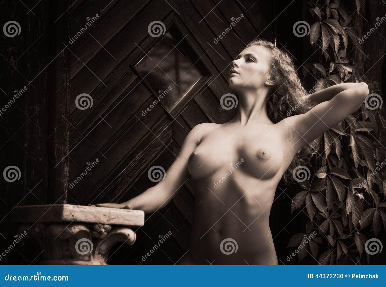 Donna nuda che posa vicino alla vecchia casa di campagna