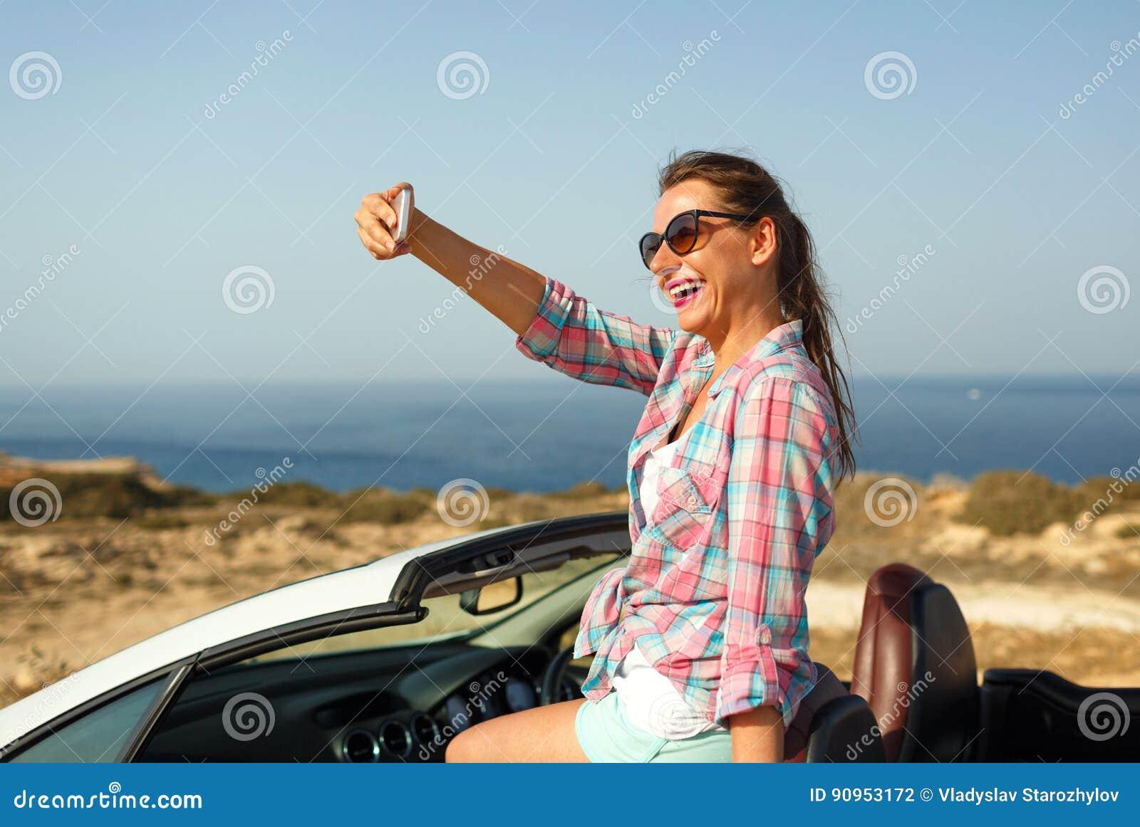 Donna in occhiali da sole che fanno autoritratto che si siede nel cabriole