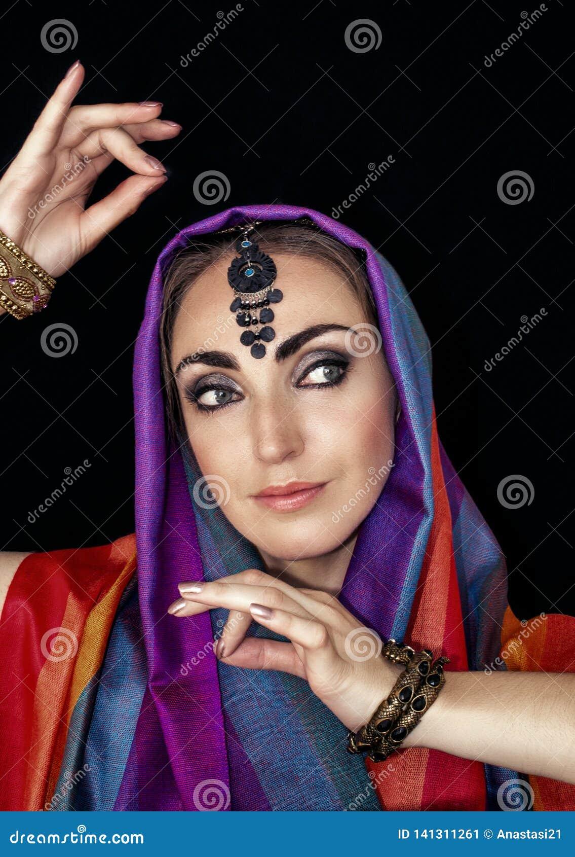 Donna orientale in burqa con i gioielli su un fondo nero
