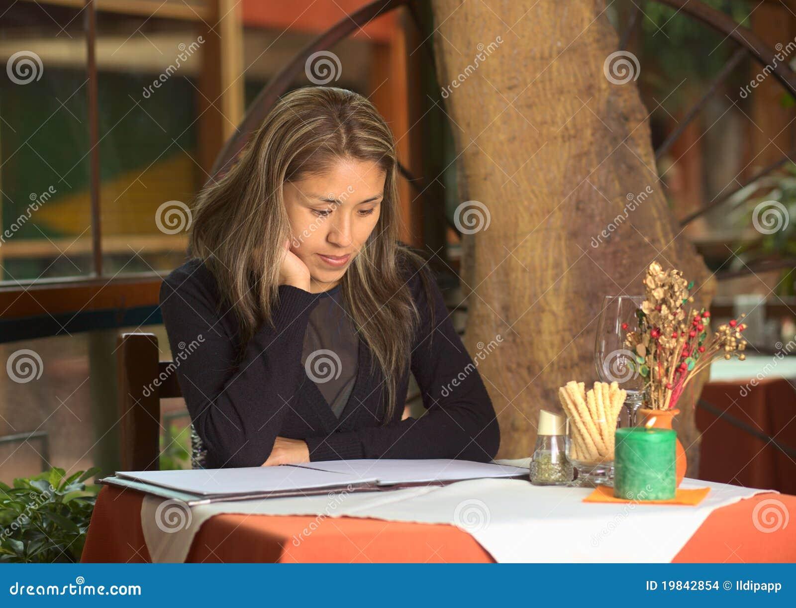 Donna peruviana che esamina il menu in un ristorante