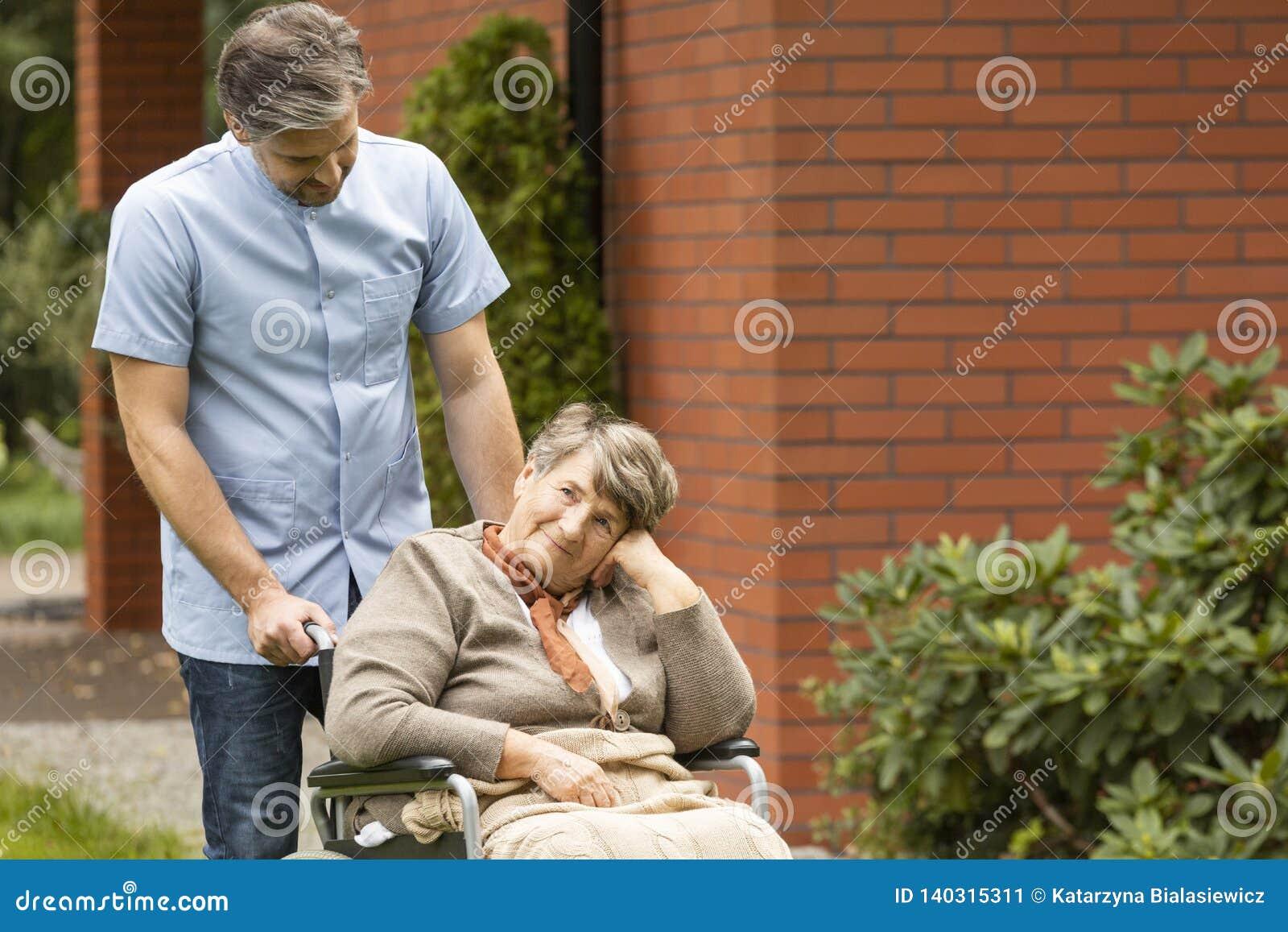 Donna più anziana nel pensiero di una sedia a rotelle e un infermiere maschio che sta accanto lei