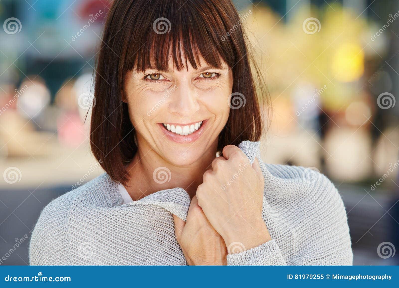 Donna più anziana sorridente che tiene maglione molle