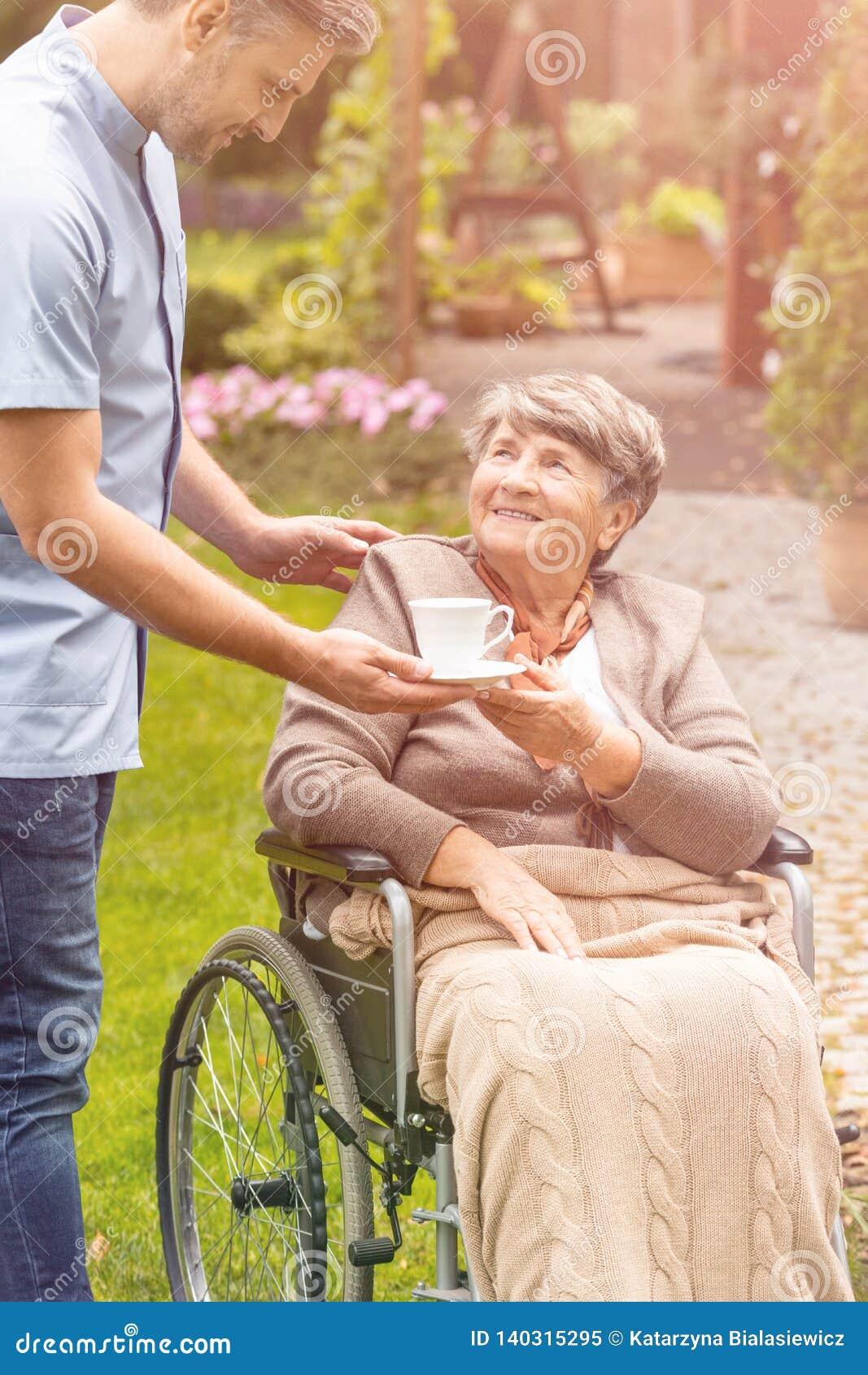 Donna più anziana in una sedia a rotelle che prende una tazza di tè da un infermiere