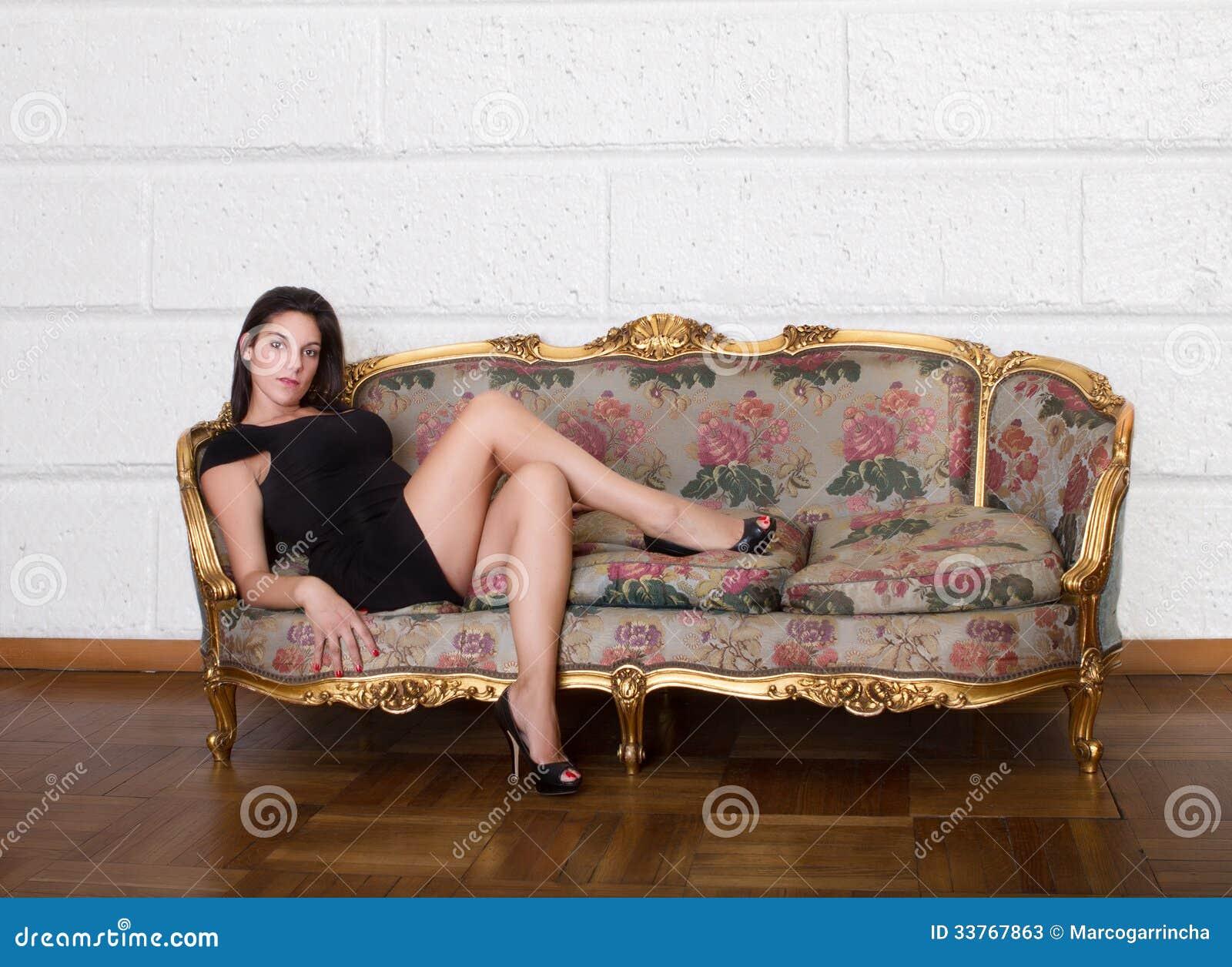 Donna piacevole che si siede sul salone