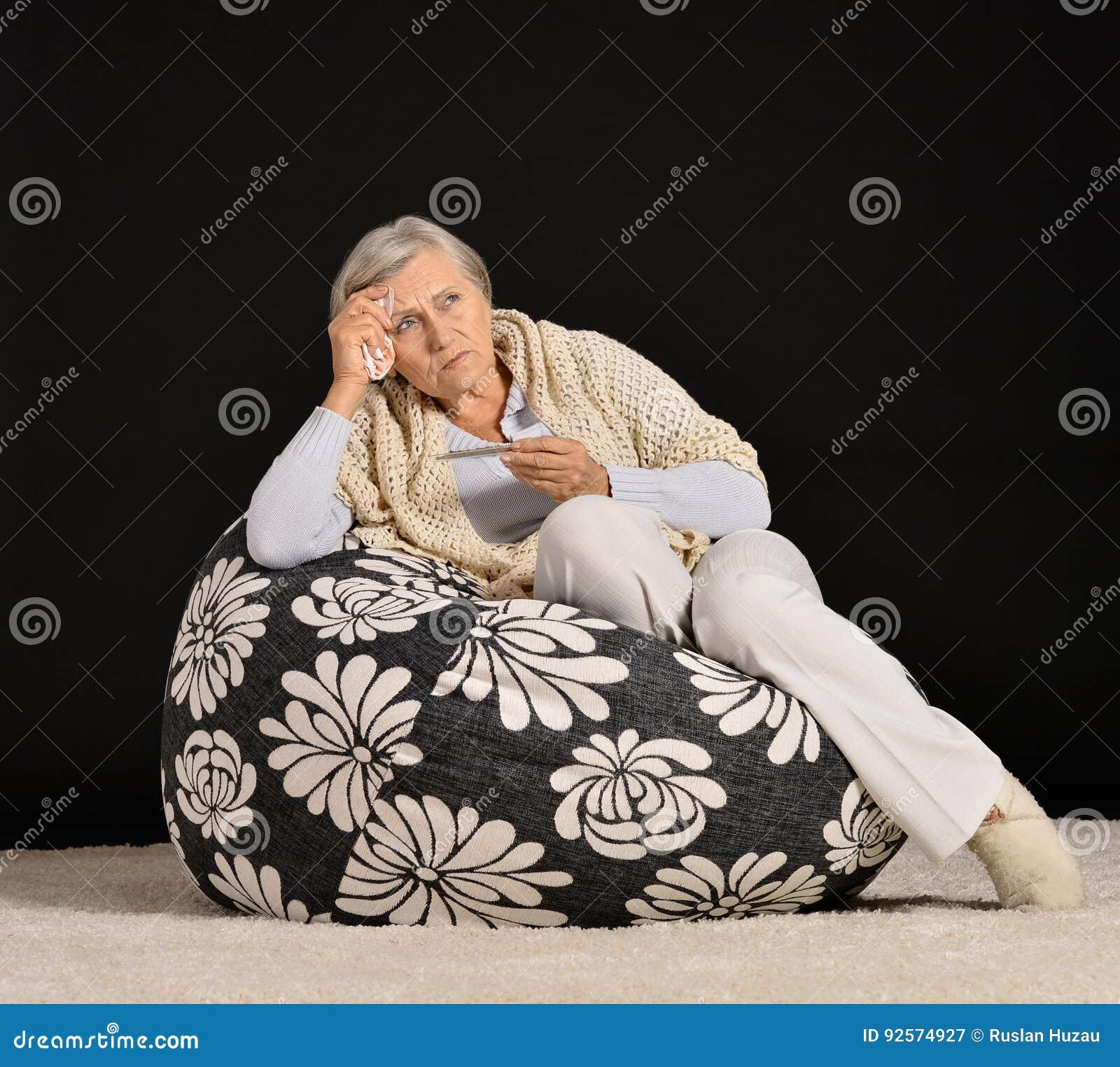 Donna senior che tricotta seduta in poltrona