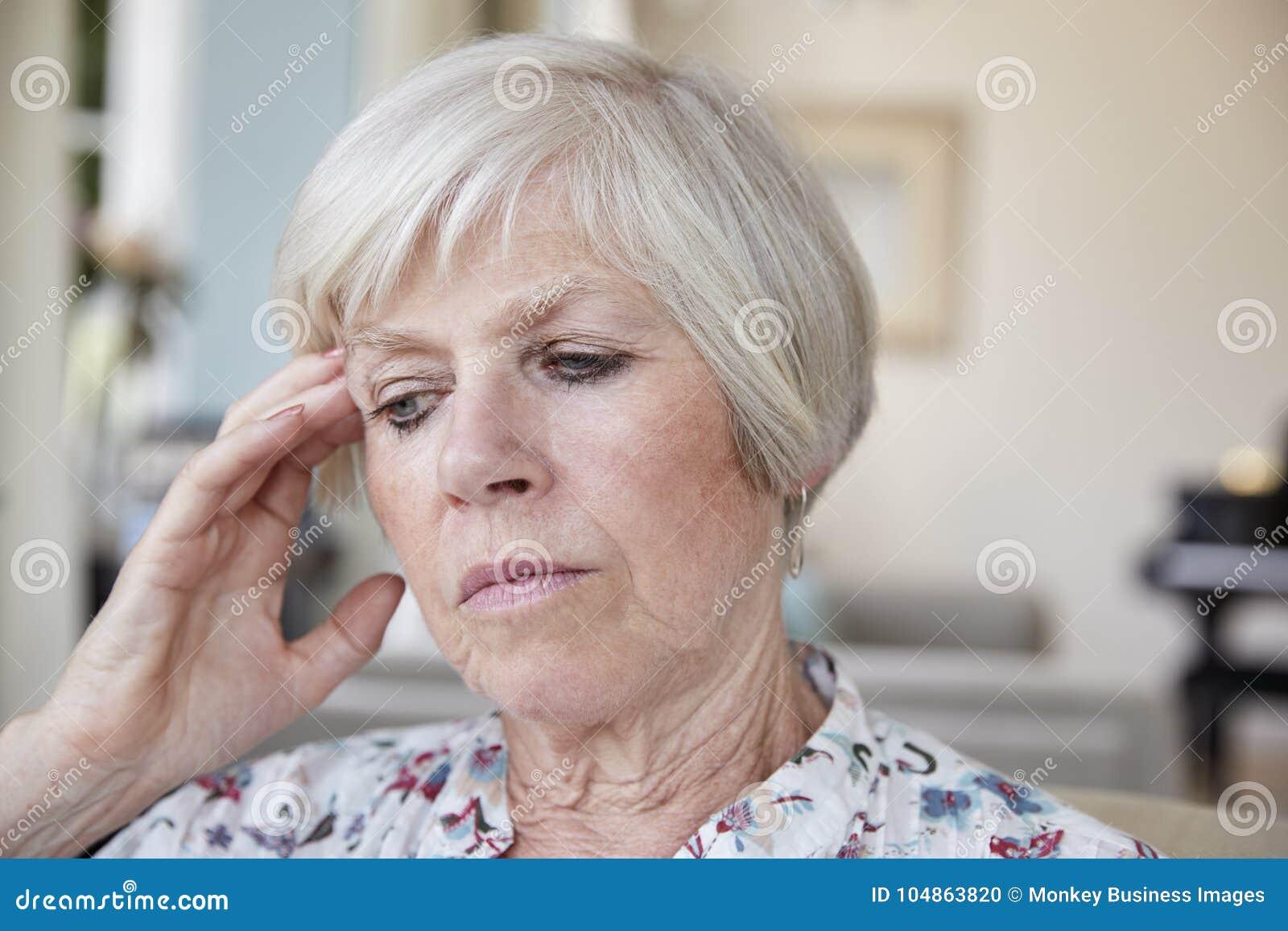 Donna senior contemplativa a casa, vicino su