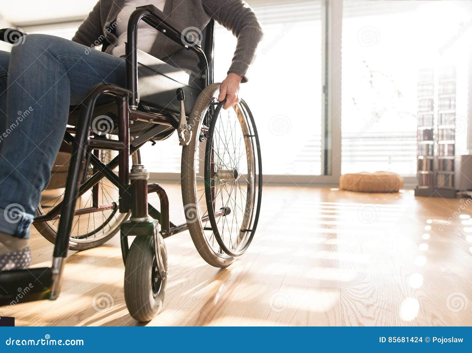 Donna senior disabile irriconoscibile in sedia a rotelle a casa