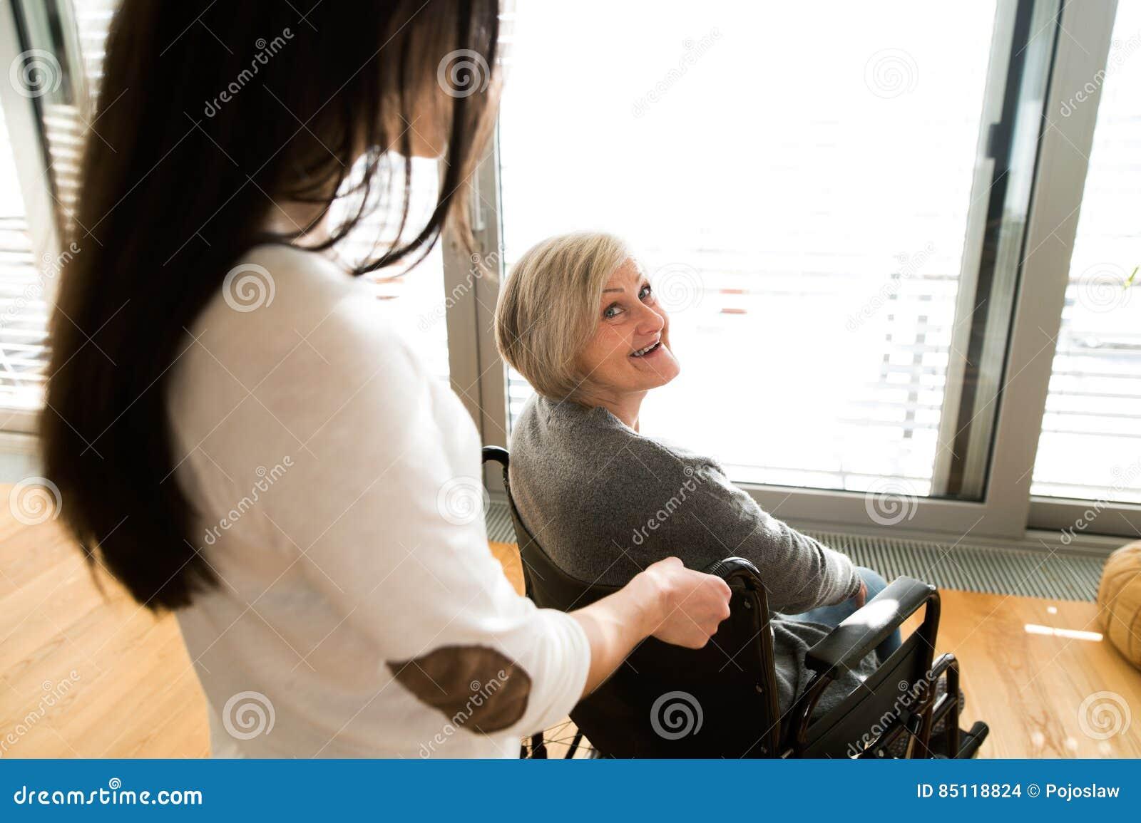 Donna senior disabile in sedia a rotelle con il suo giovane daugher