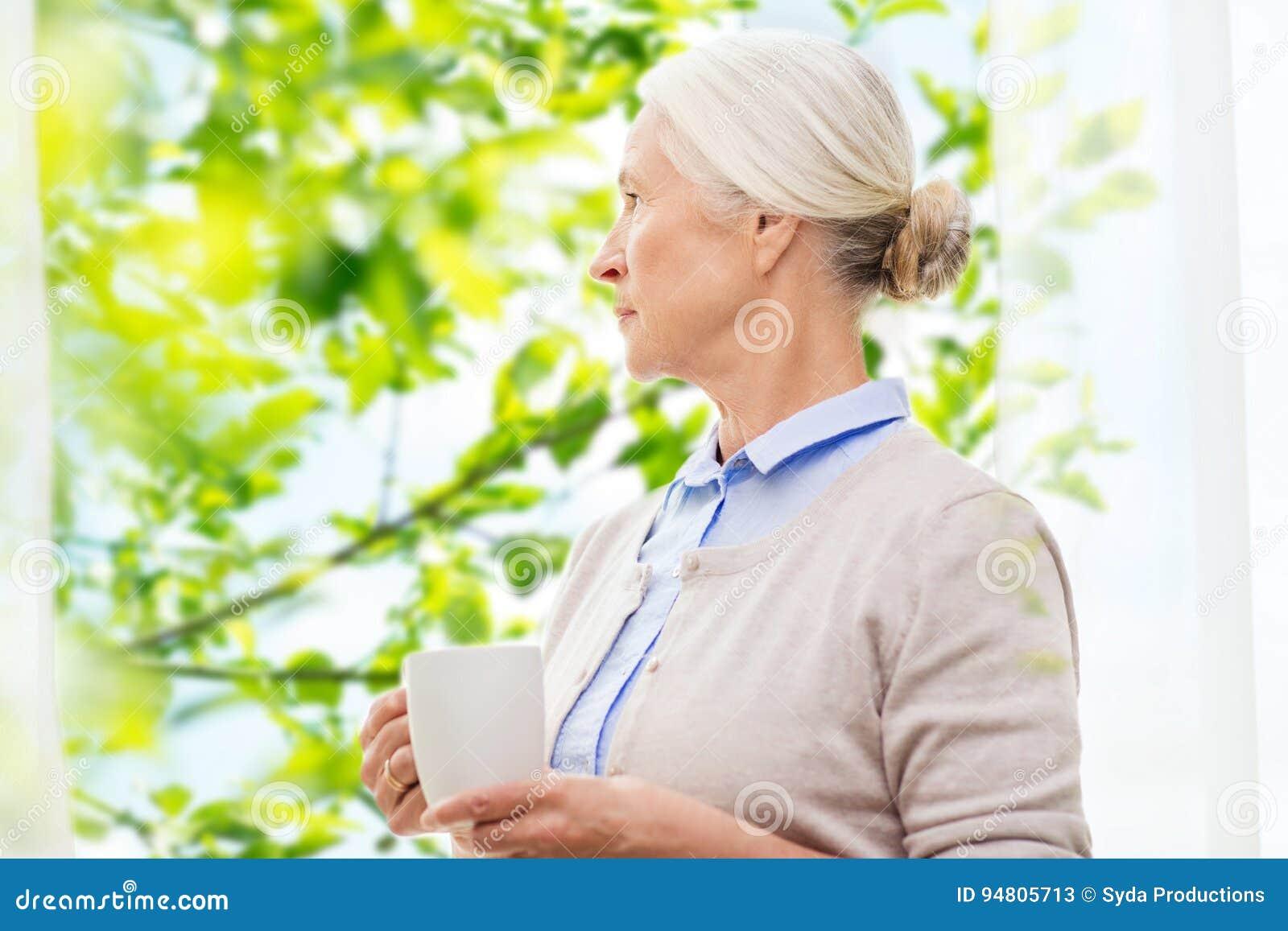 Donna senior sola con la tazza di tè o di caffè
