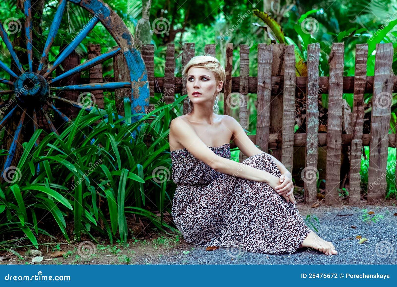 Donna sensuale che si siede nella foresta