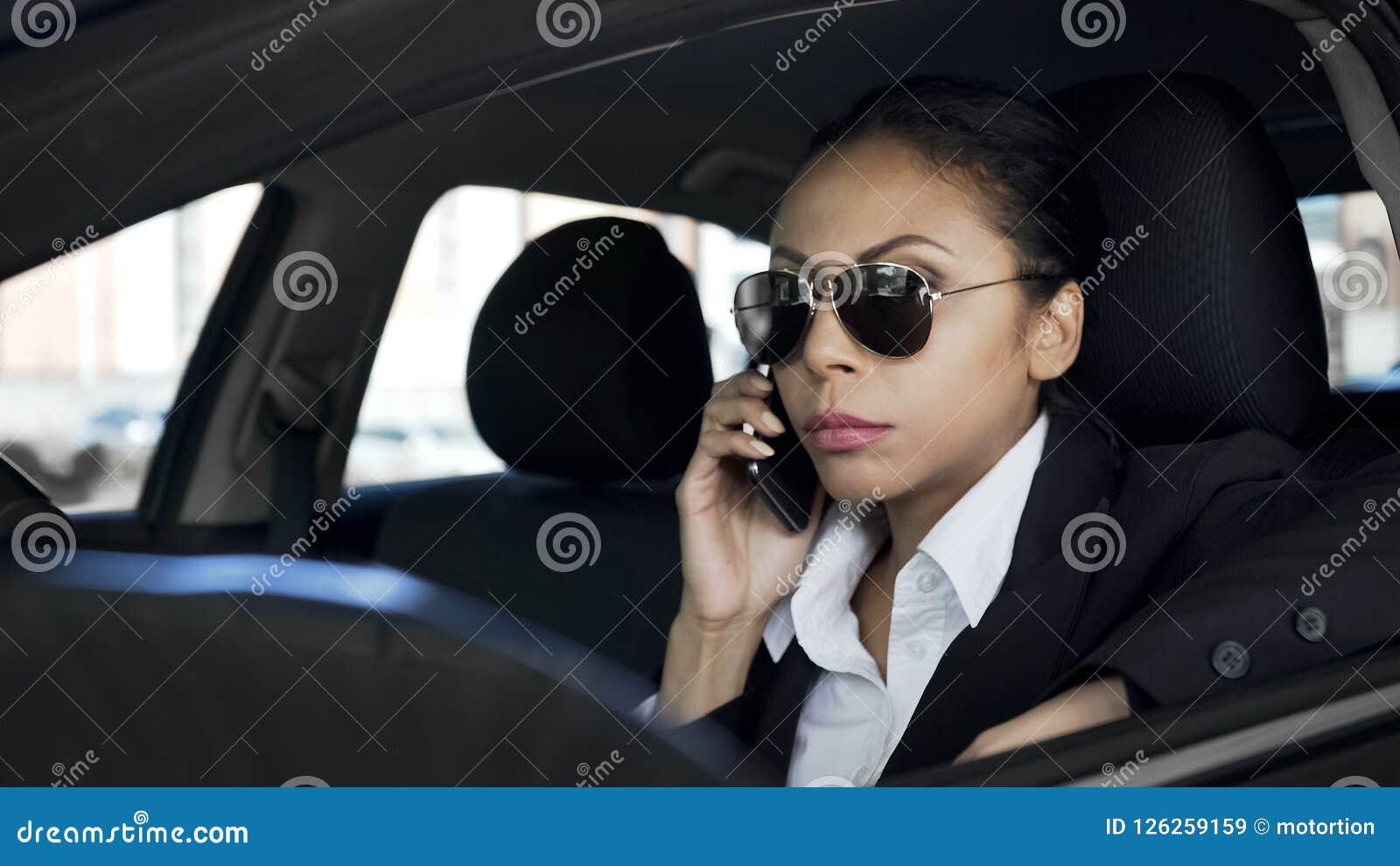 Donna seria che parla sul telefono in automobile, agente investigativo privato che spia, agente di polizia