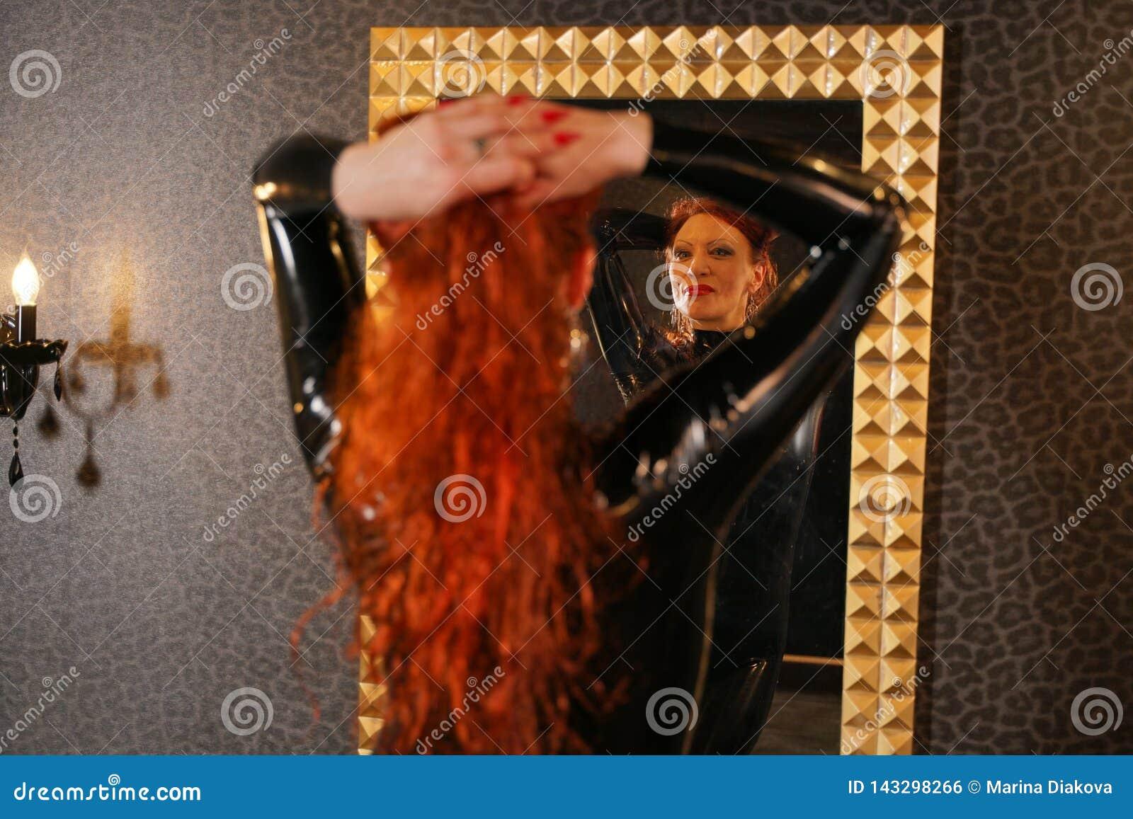 Donna sessuale della testarossa del feticcio che indossa il catsuit di gomma del lattice nero e che esamina lo specchio nella sta