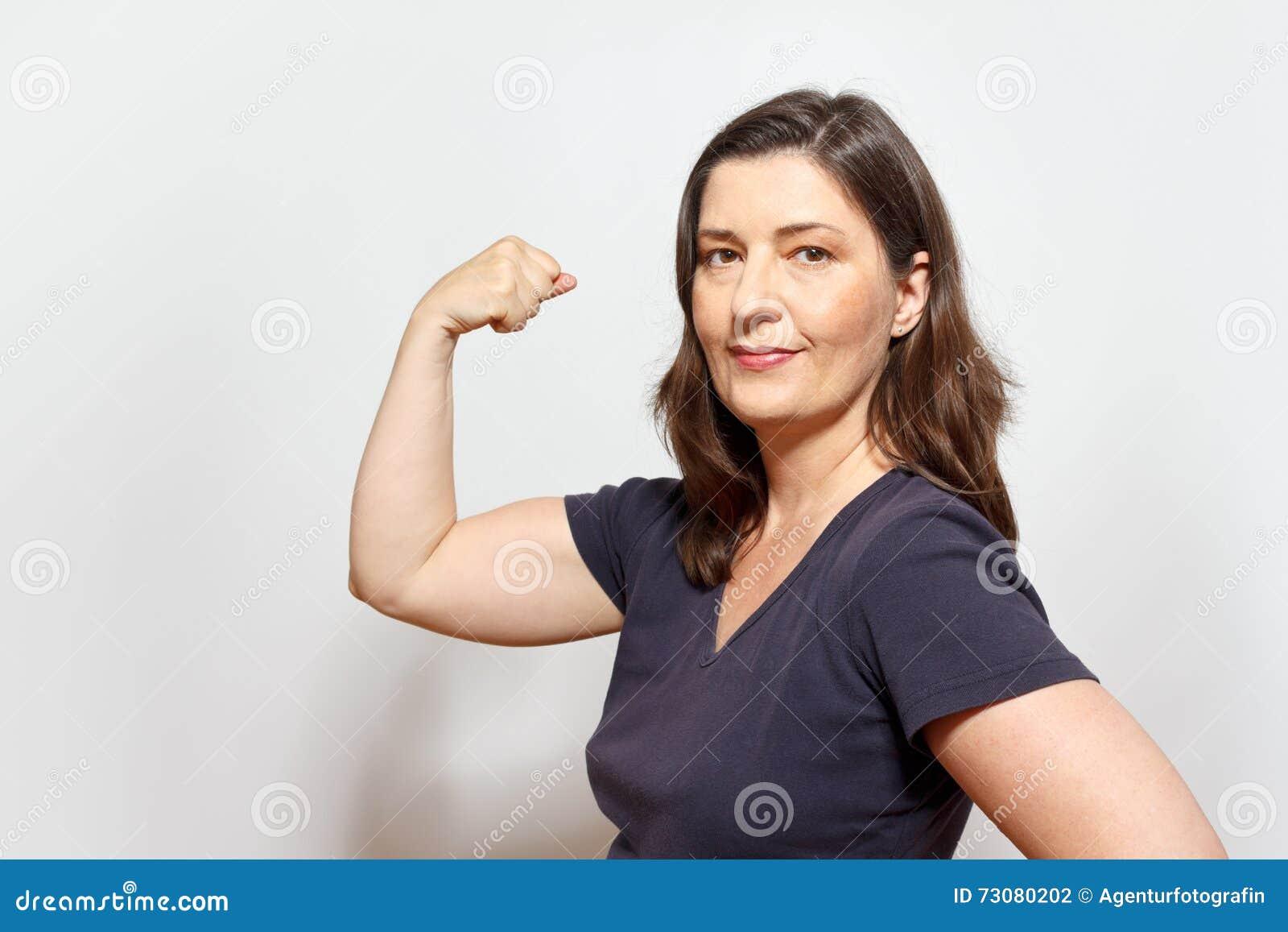 Donna sicura di sé che flette i muscoli del bicipite