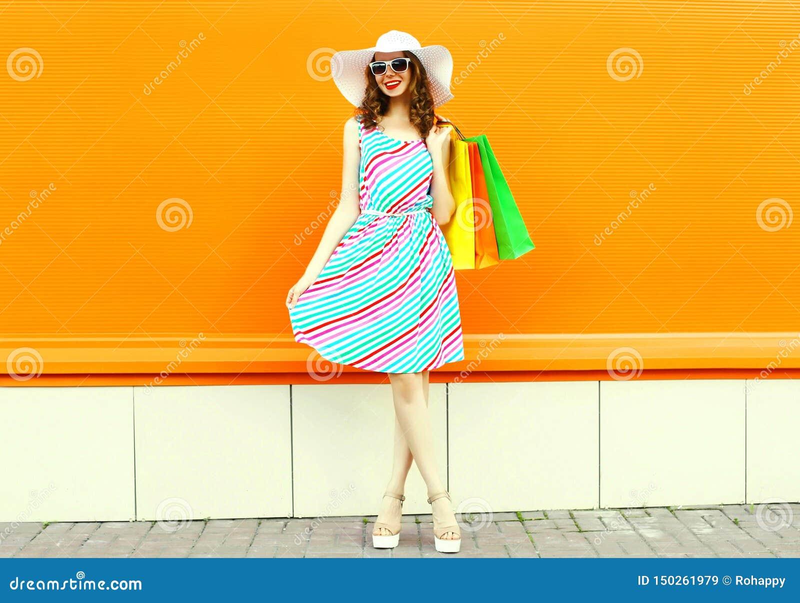 Donna sorridente alla moda con i sacchetti della spesa che portano vestito a strisce variopinto, cappello di paglia di estate che