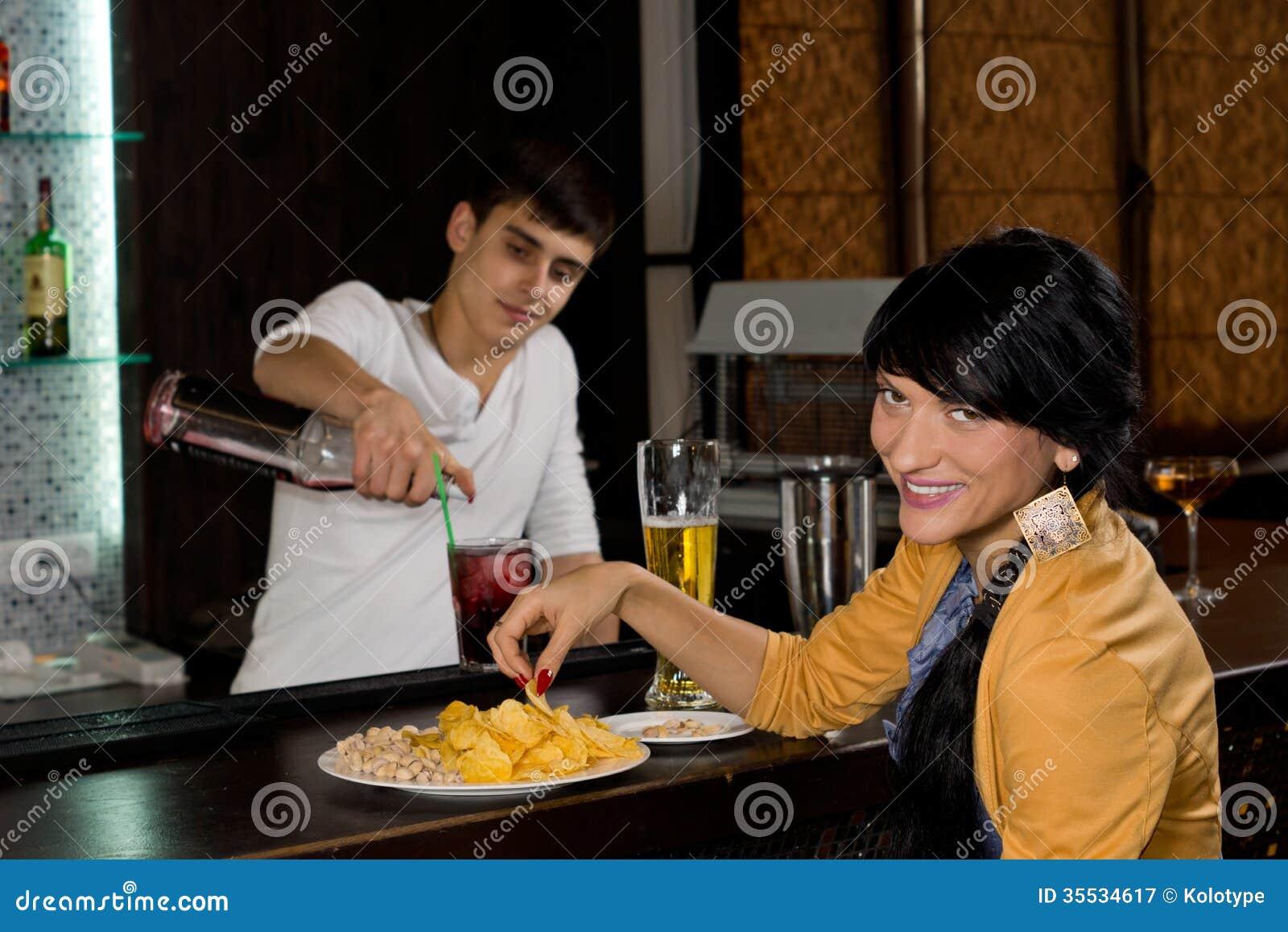 Donna sorridente amichevole che si siede ad una barra