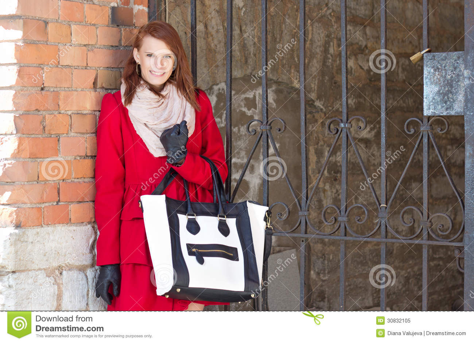 Donna sorridente attraente sopra il muro di mattoni rosso