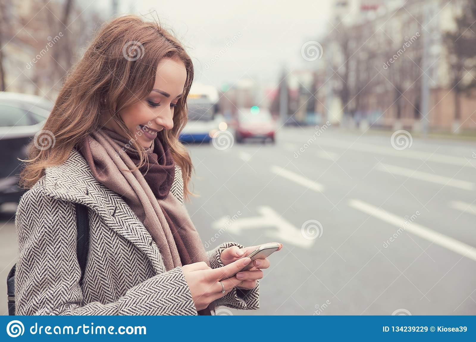 Donna sorridente che controlla email tramite telefono cellulare che aspetta un bus