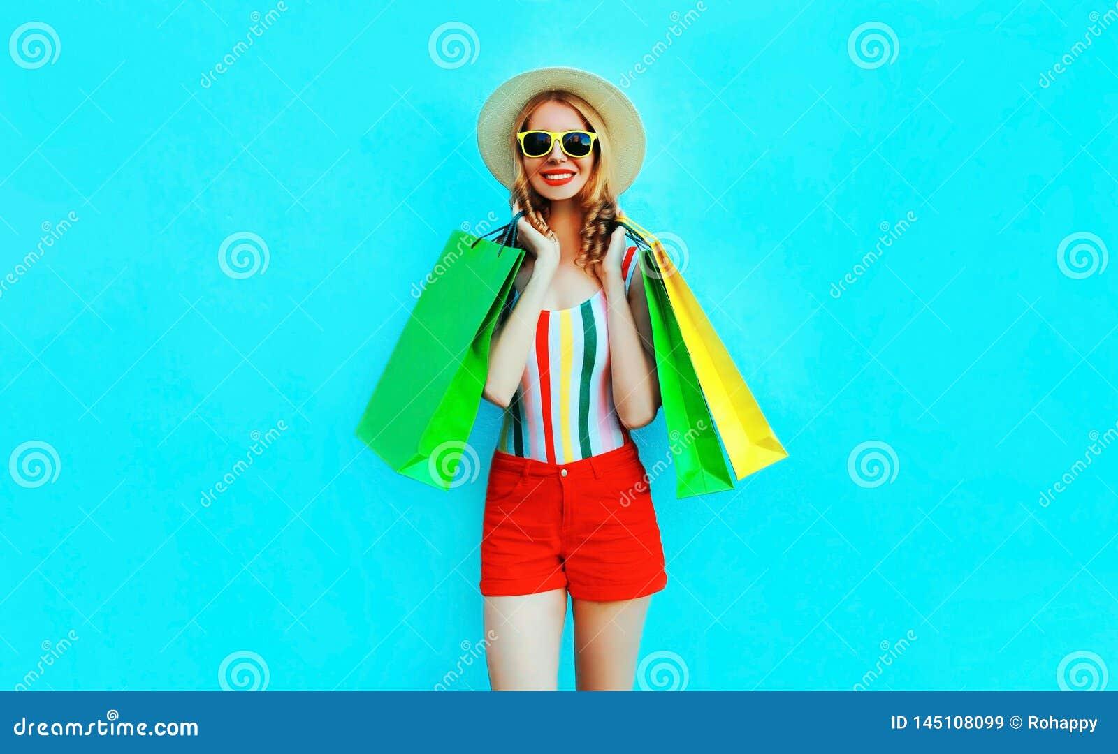 Donna sorridente felice del ritratto la giovane con i sacchetti della spesa in maglietta variopinta, il cappello del giro dell es