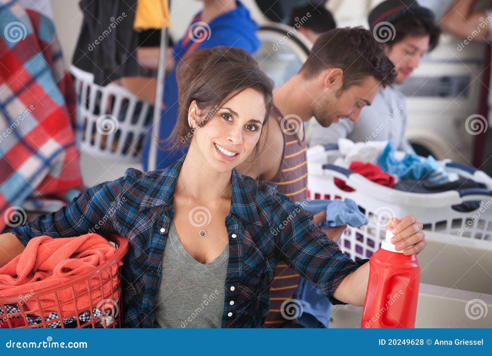 Donna sorridente in lavanderia automatica
