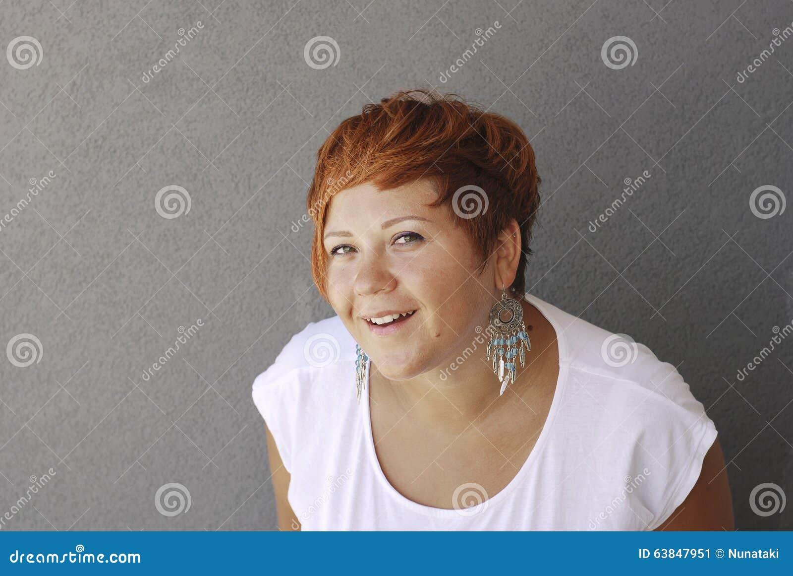Donna sorridente su una priorità bassa grigia