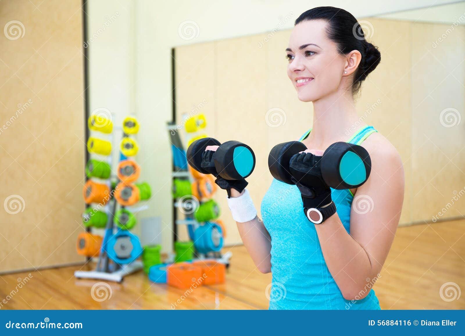 Donna sportiva felice che si esercita con la testa di legno in palestra