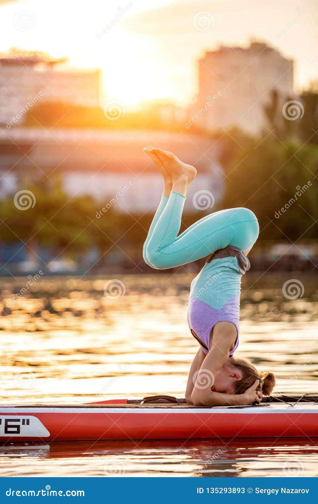 Donna sportiva nella posizione di yoga sul paddleboard, facente yoga sul bordo del sup, esercizio per flessibilità ed allungament