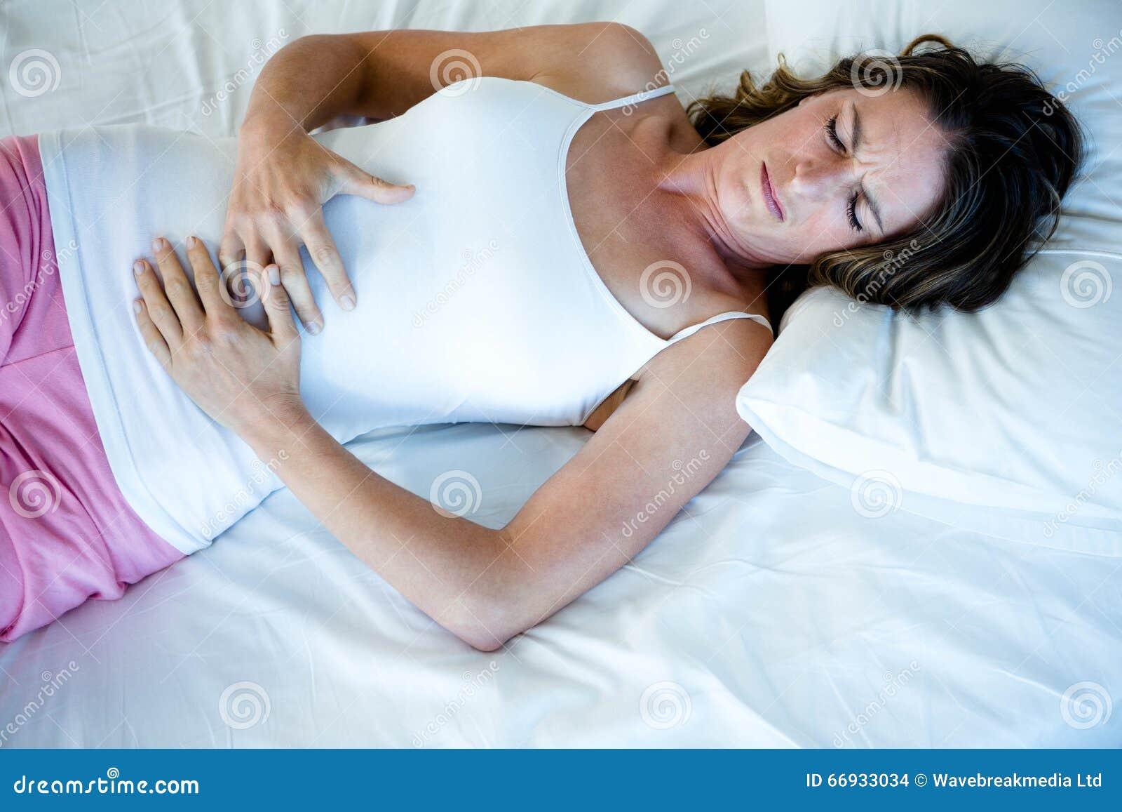Donna stanca che si trova a letto innestando il suo stomaco fotografia stock immagine di - Giochi che si baciano a letto ...