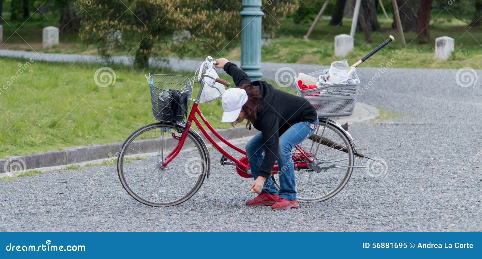 Donna su un bycicle in giardino di pietra