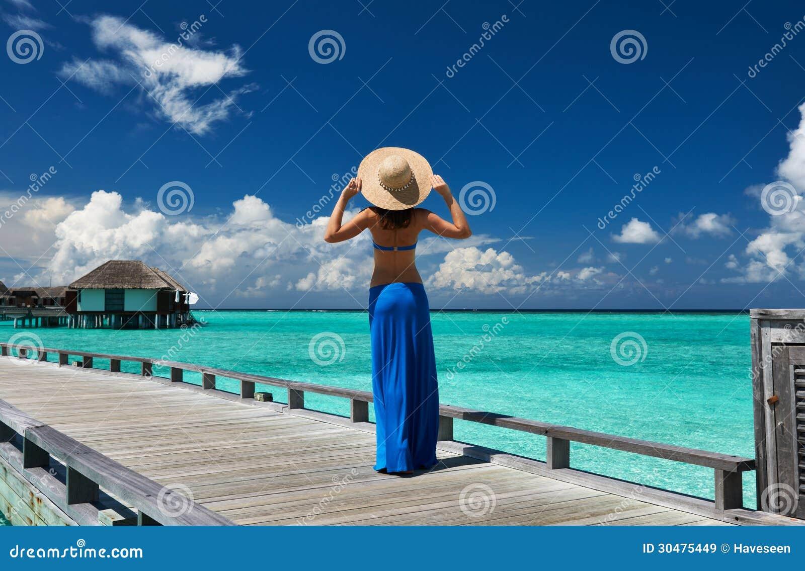 Donna su un molo della spiaggia alle Maldive