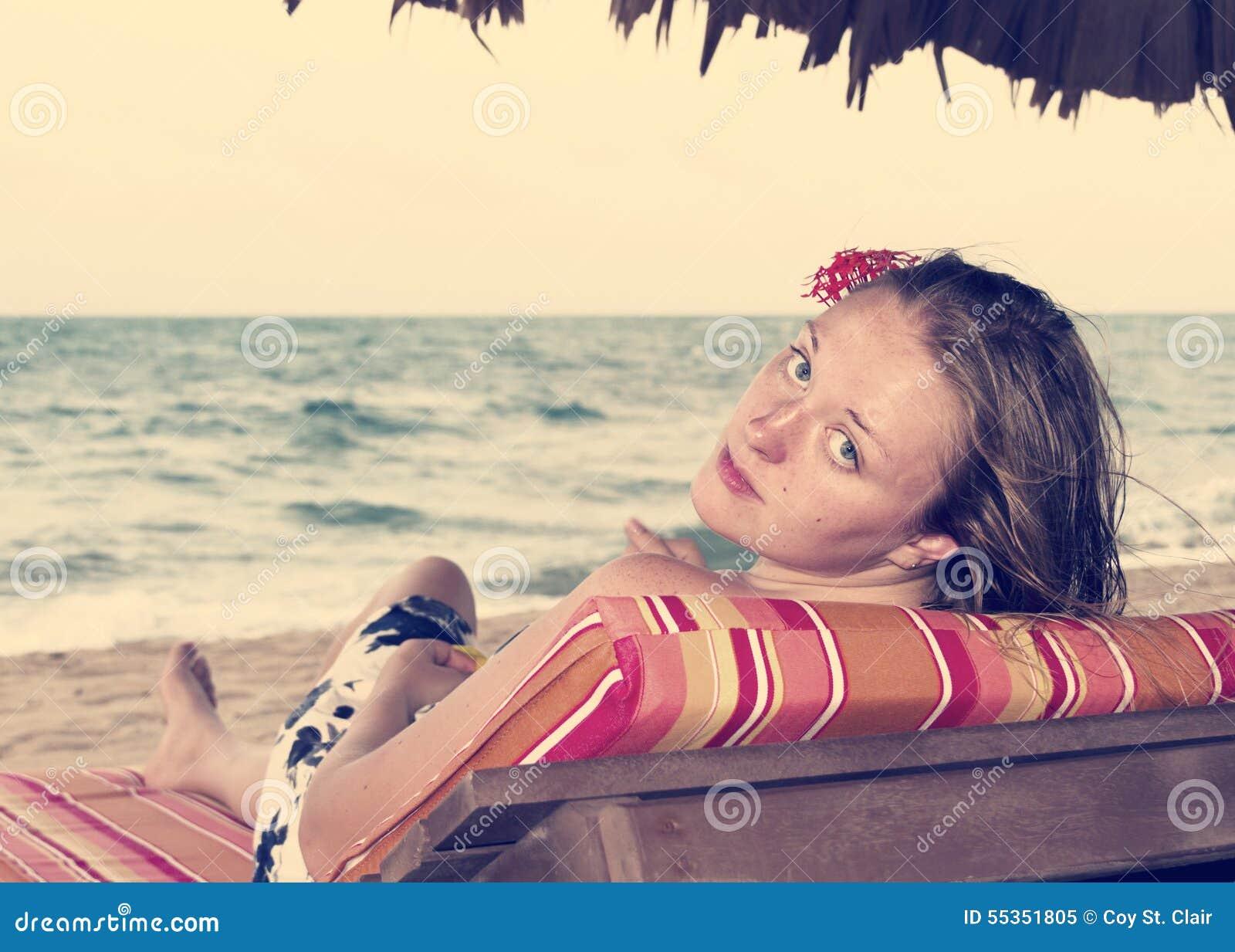 Donna su una sedia dall oceano con un fiore in suoi capelli, retro