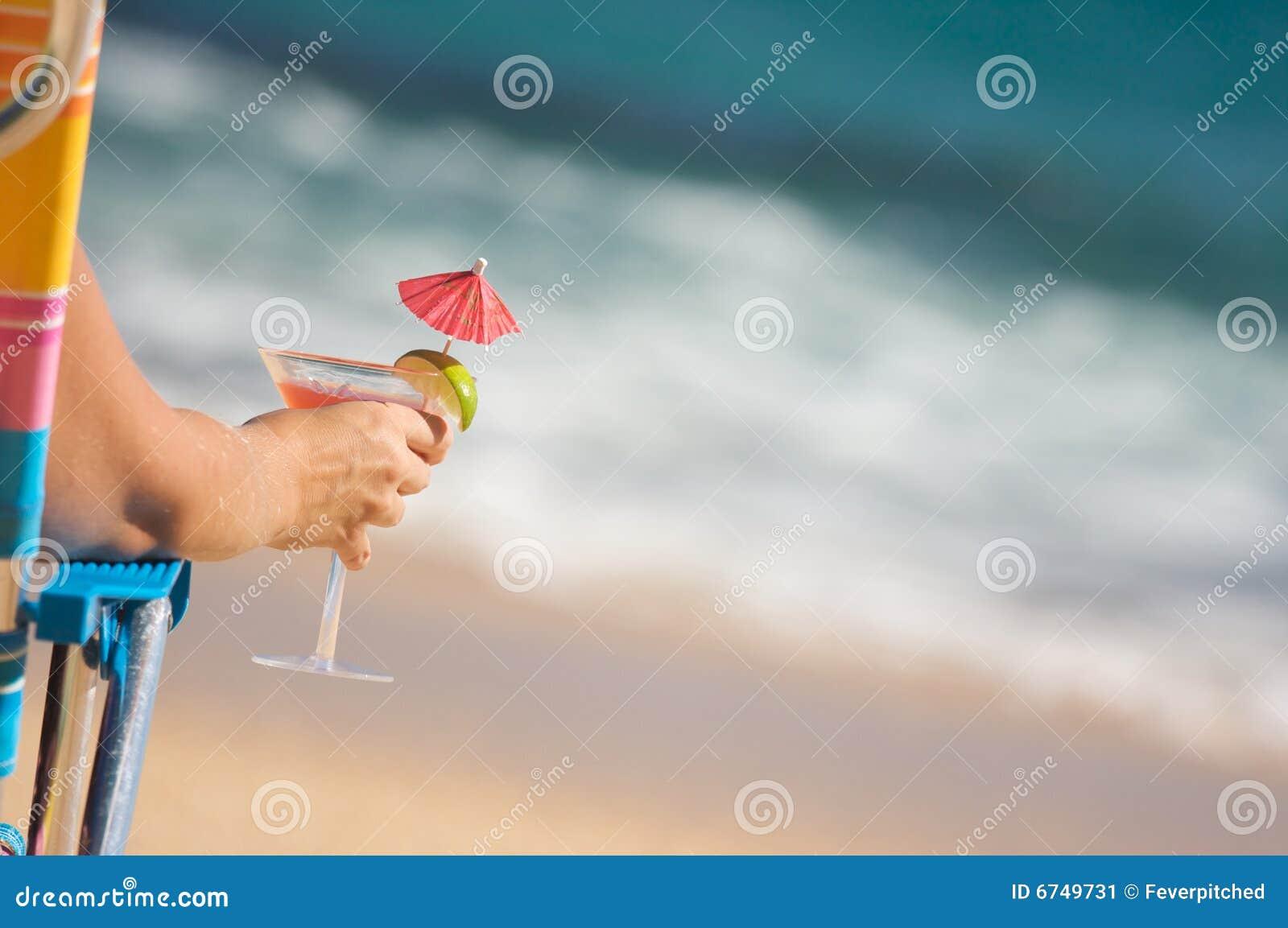 Donna sulla spiaggia con la bevanda tropicale