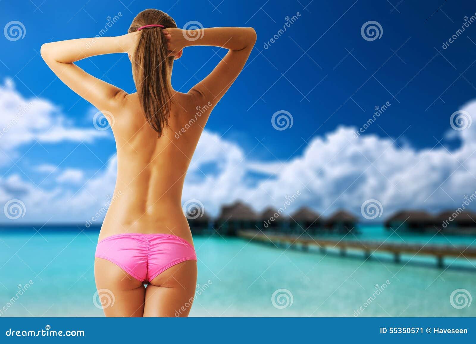 Donna topless sulla bella spiaggia con i bungalow dell acqua