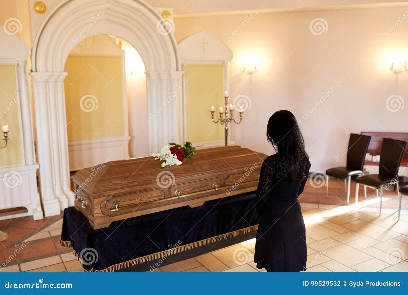 Donna triste con la bara al funerale in chiesa