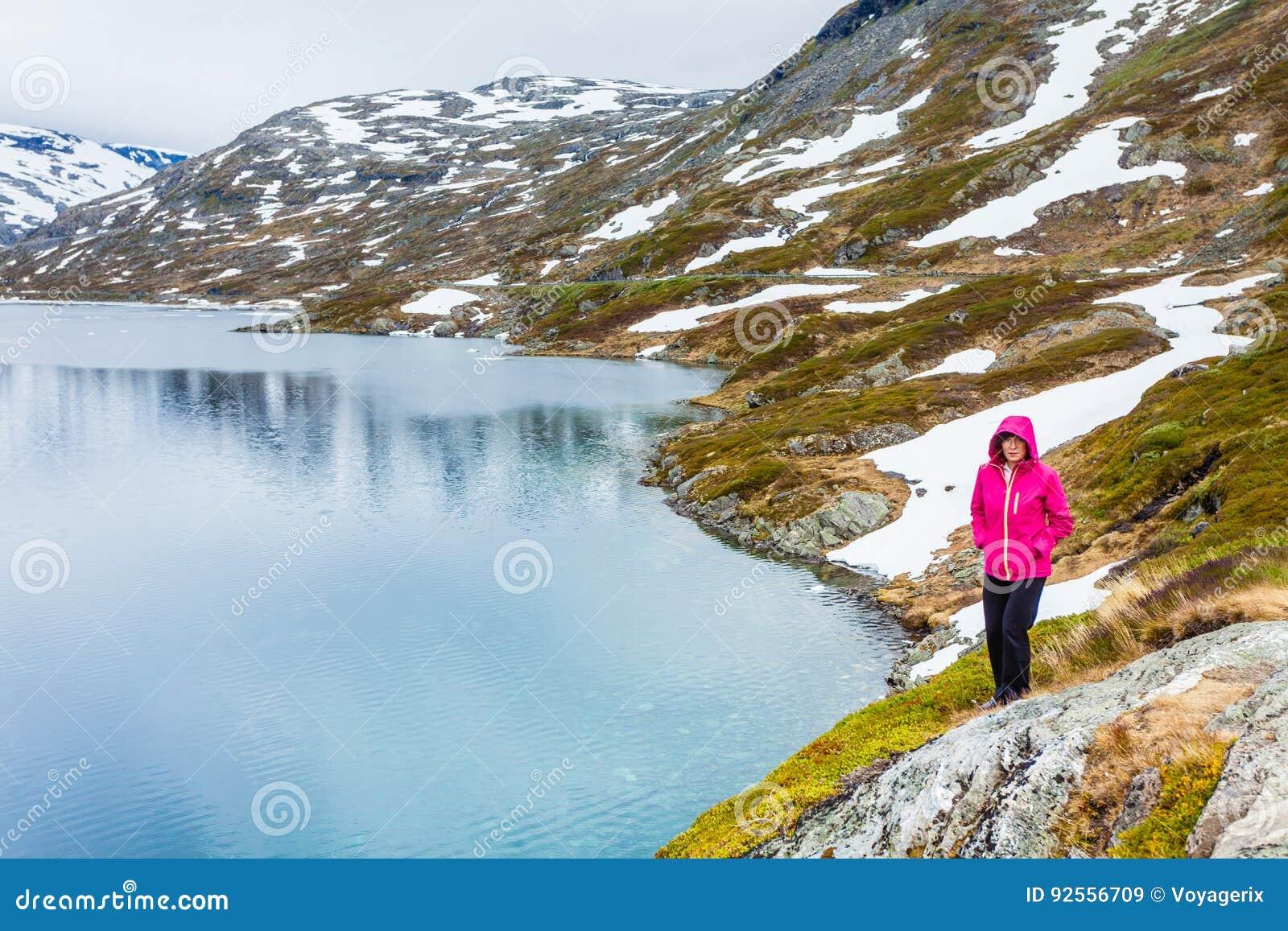 Donna turistica che fa una pausa il lago Djupvatnet, Norvegia