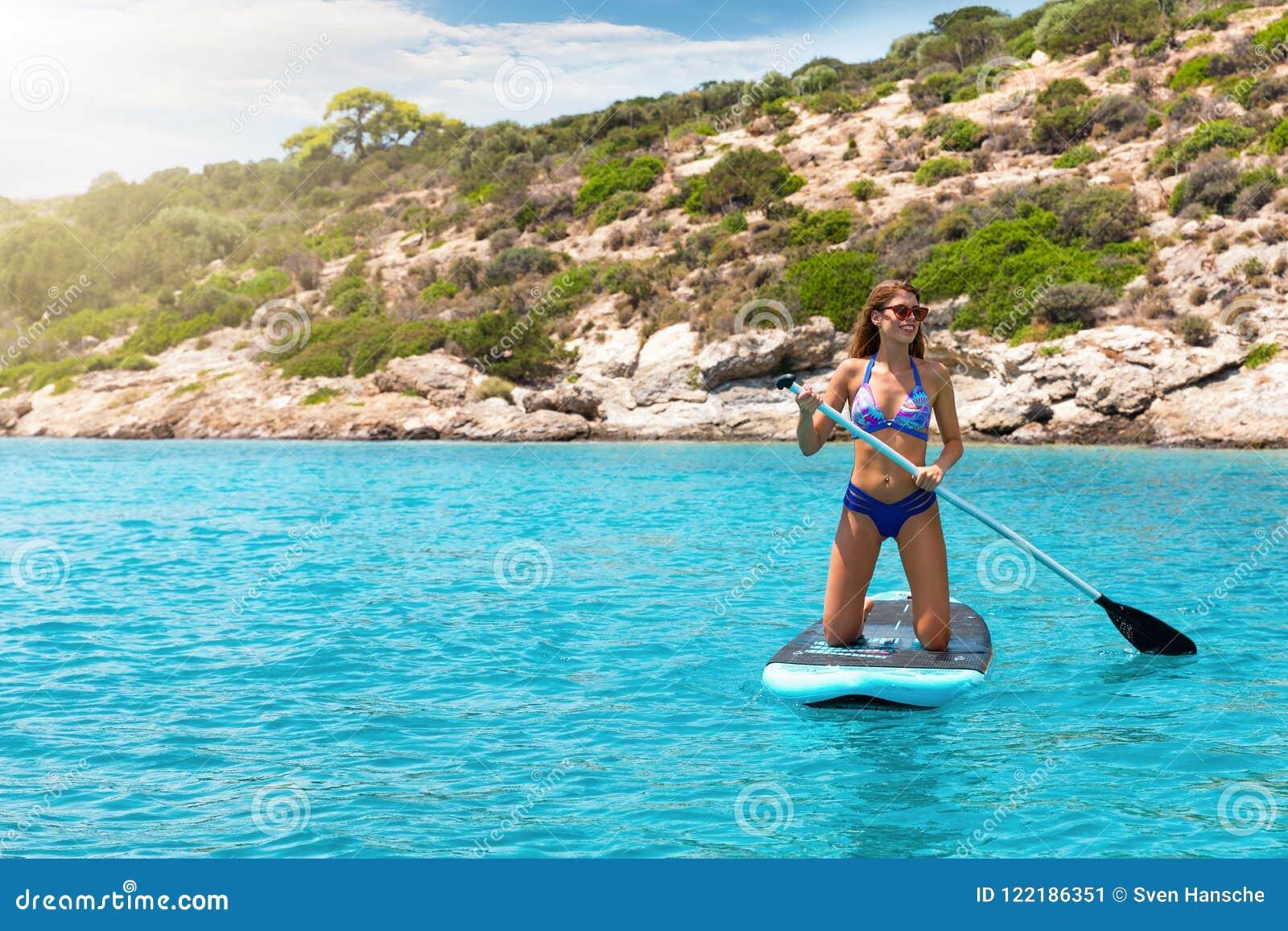 Donna in un bikini su un supporto sul bordo di pagaia sopra turchese, acque Mediterranee
