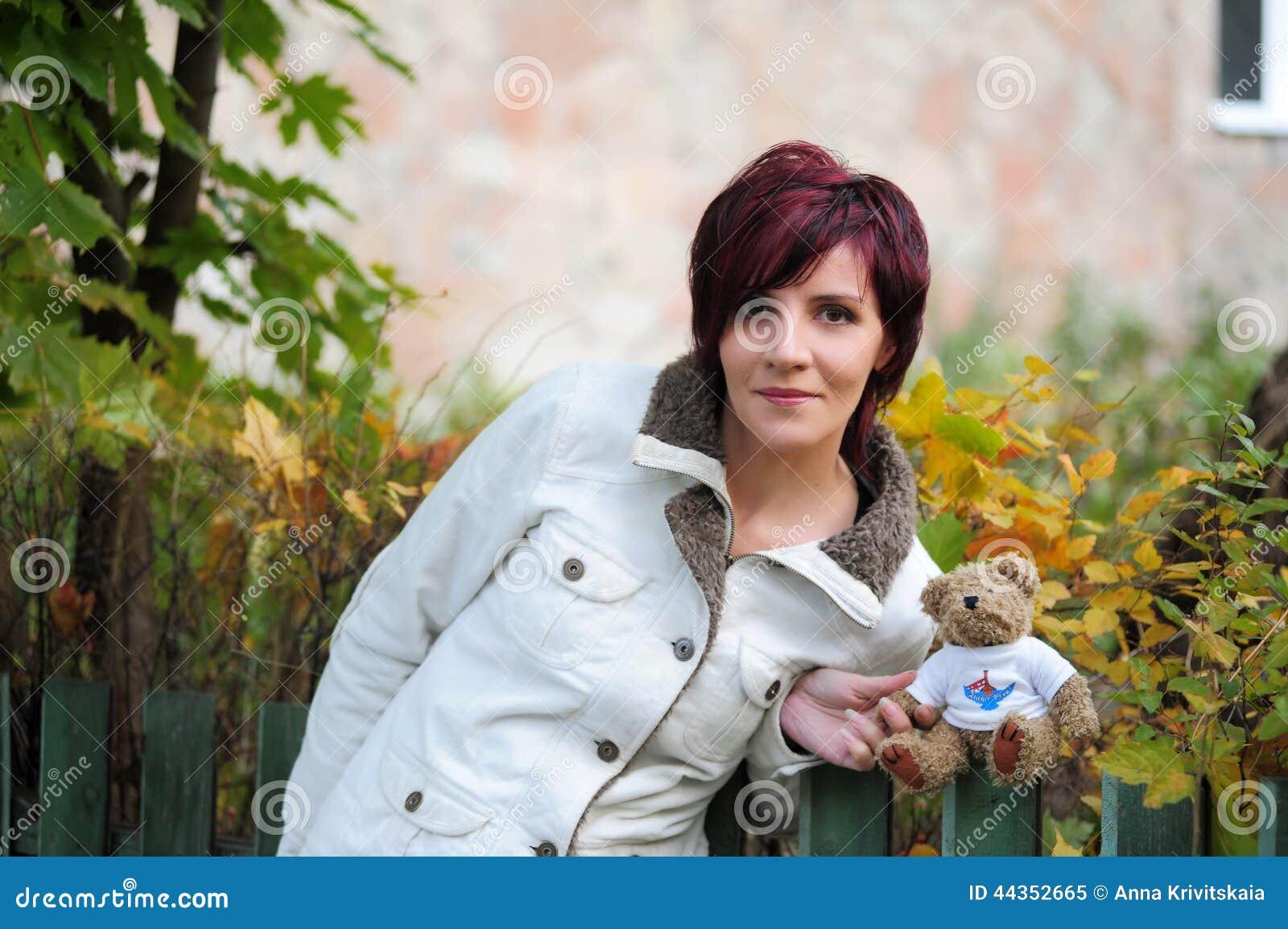 Donna in un rivestimento bianco con l orsacchiotto