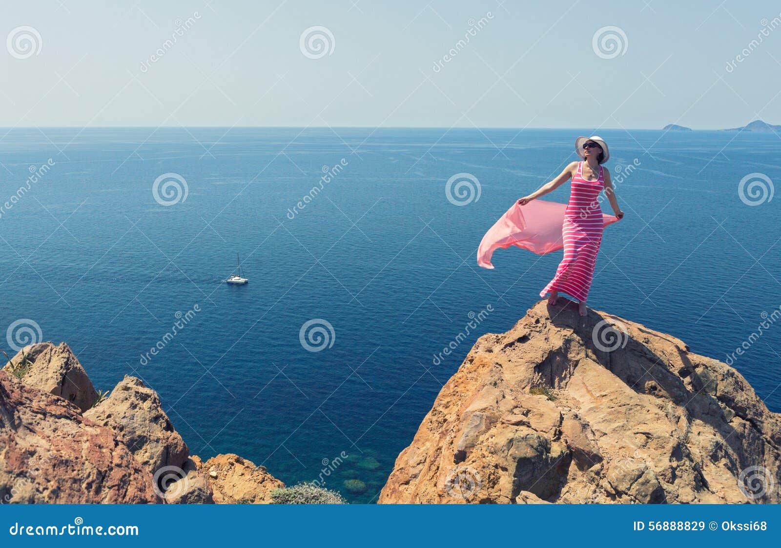 Donna in un vestito lungo che sta su un mare della roccia