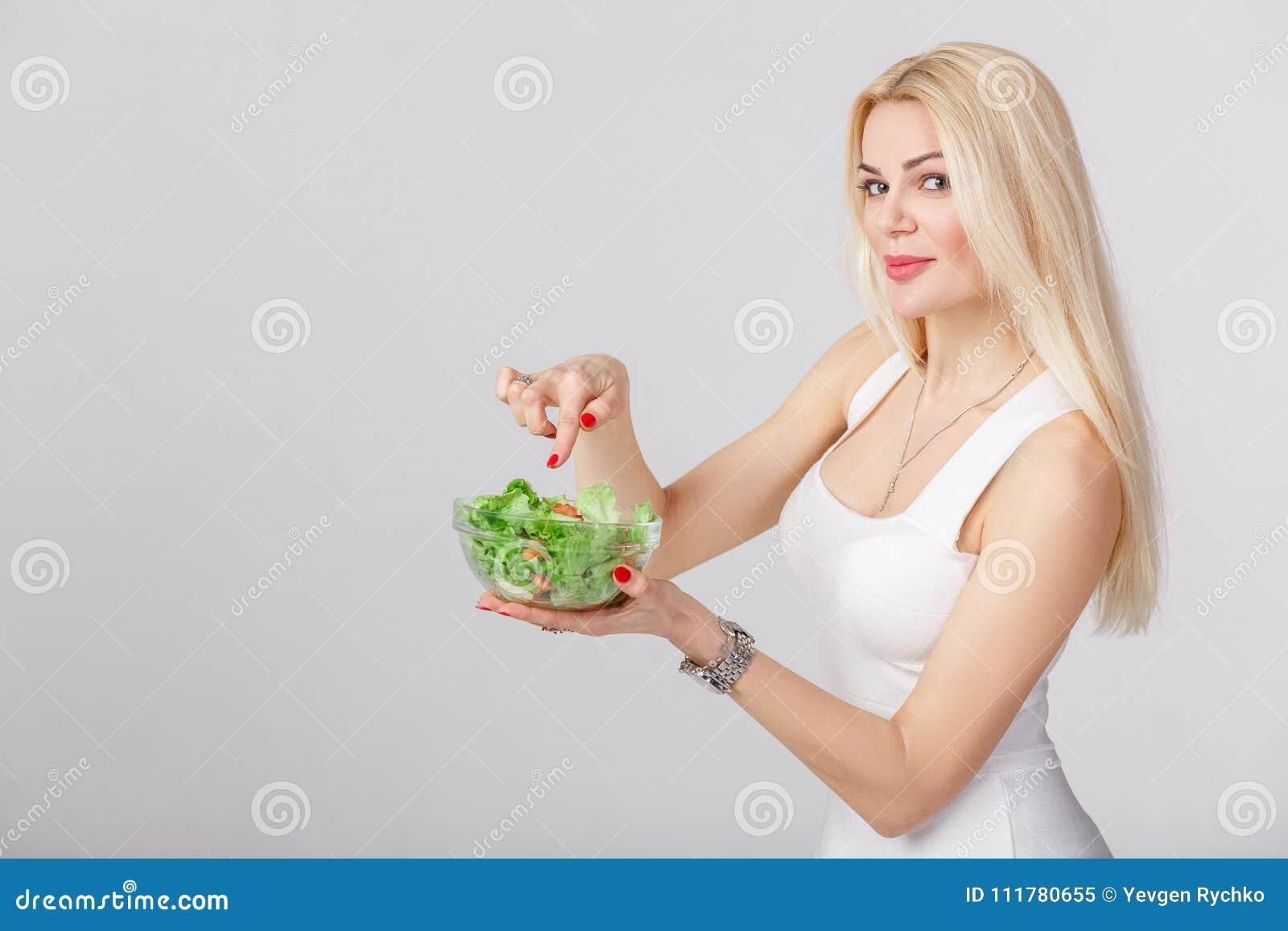 Donna in vestito bianco con insalata fresca